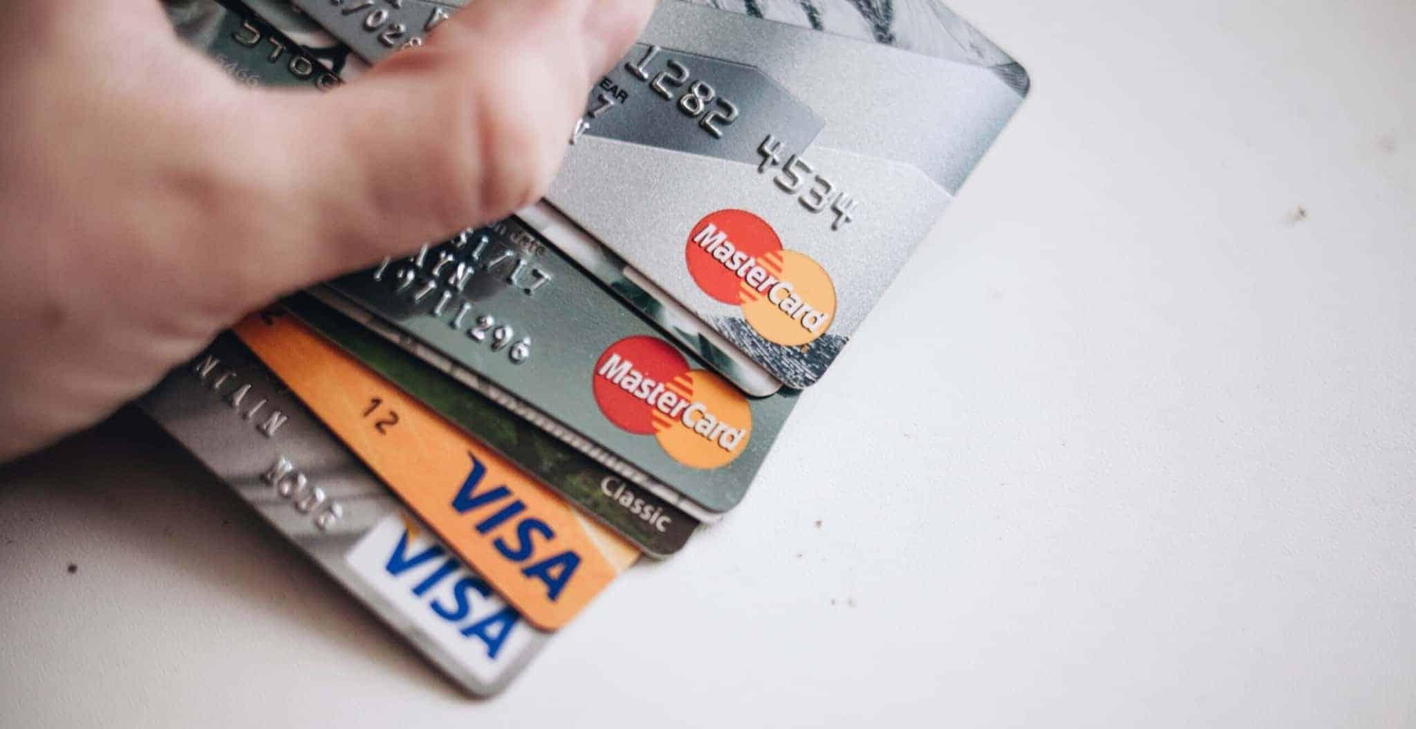 mão de pessoa segura vários cartões de crédito visa e mastercard