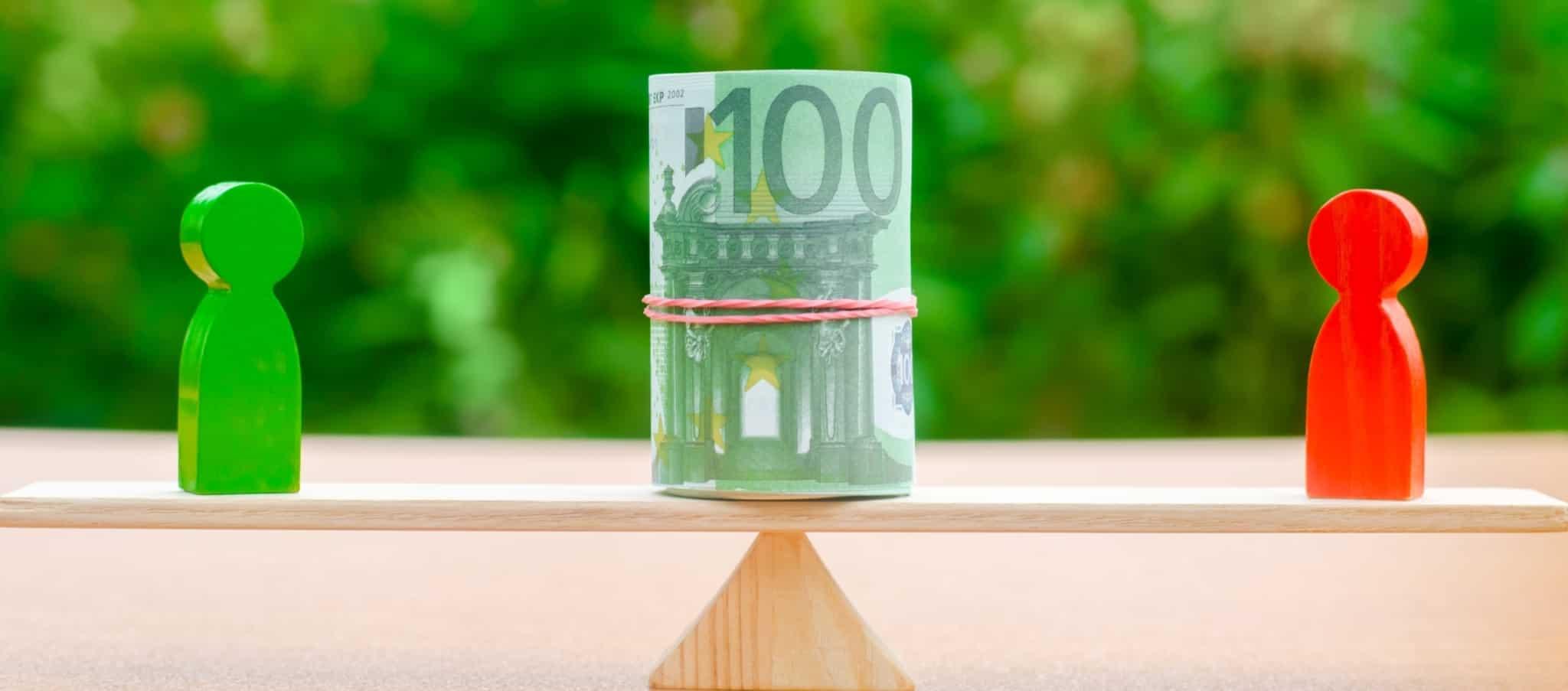 balança de madeira com um rolo de notas de 100 euros e duas figuras em madeira