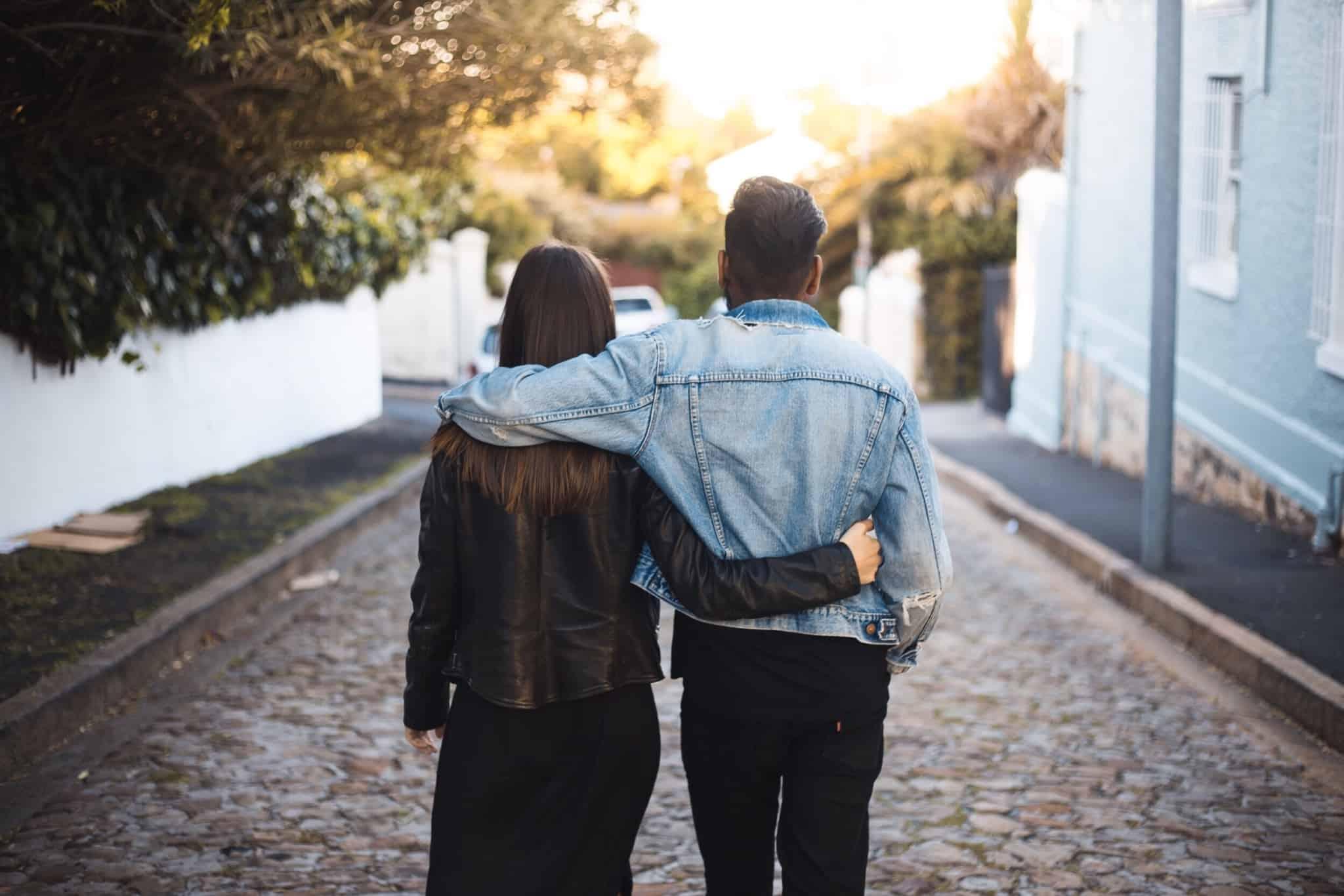 casal de costas a andar na rua com os braços à volta um do outro