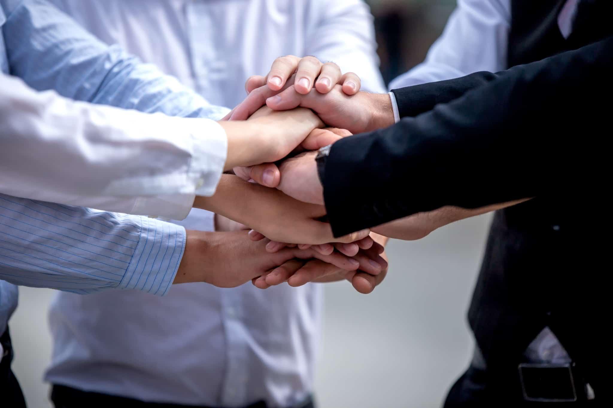 Homens-de-negocios-com-as-maos-em-sinal-da-uniao