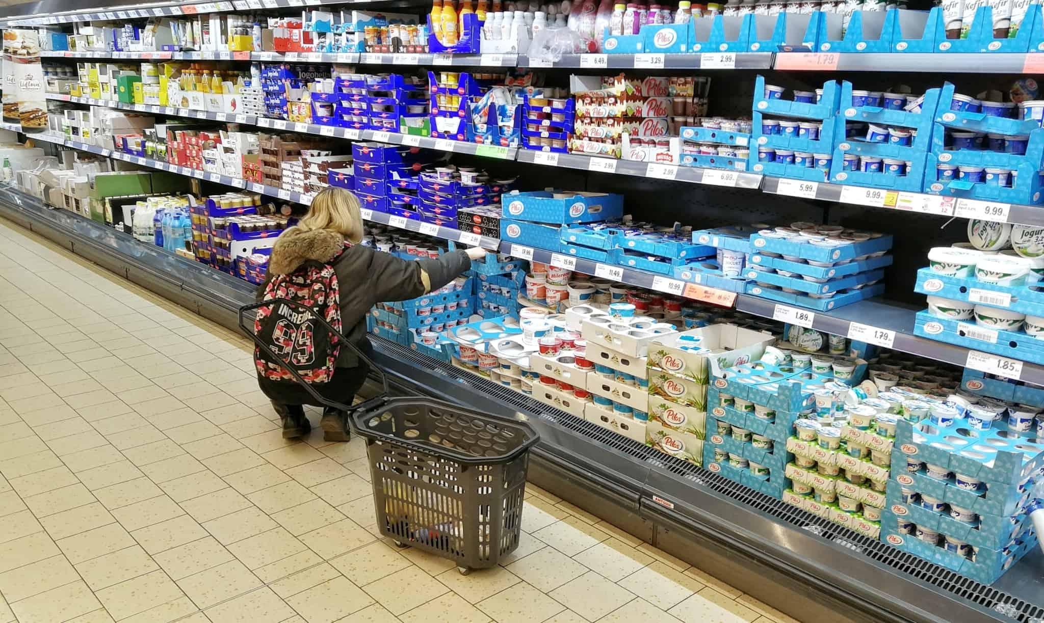 mulher a escolher iogurtes no supermercado