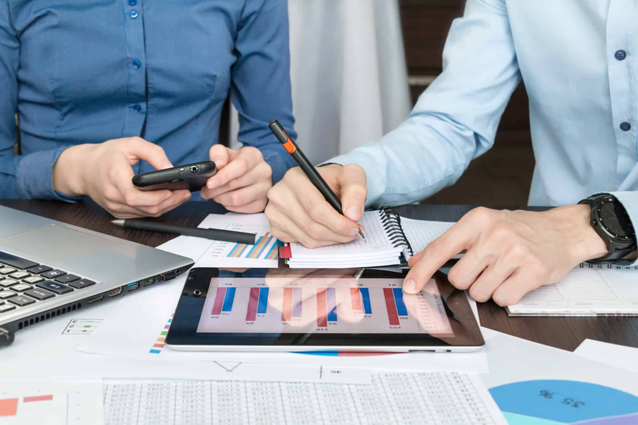 dois homens trabalham com um gráfico que aparece no tablet
