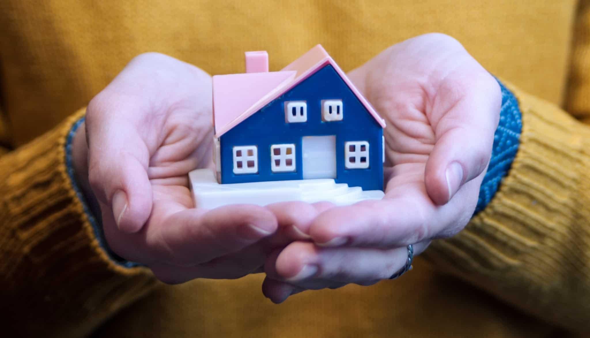 Duas mãos a segurar uma casa