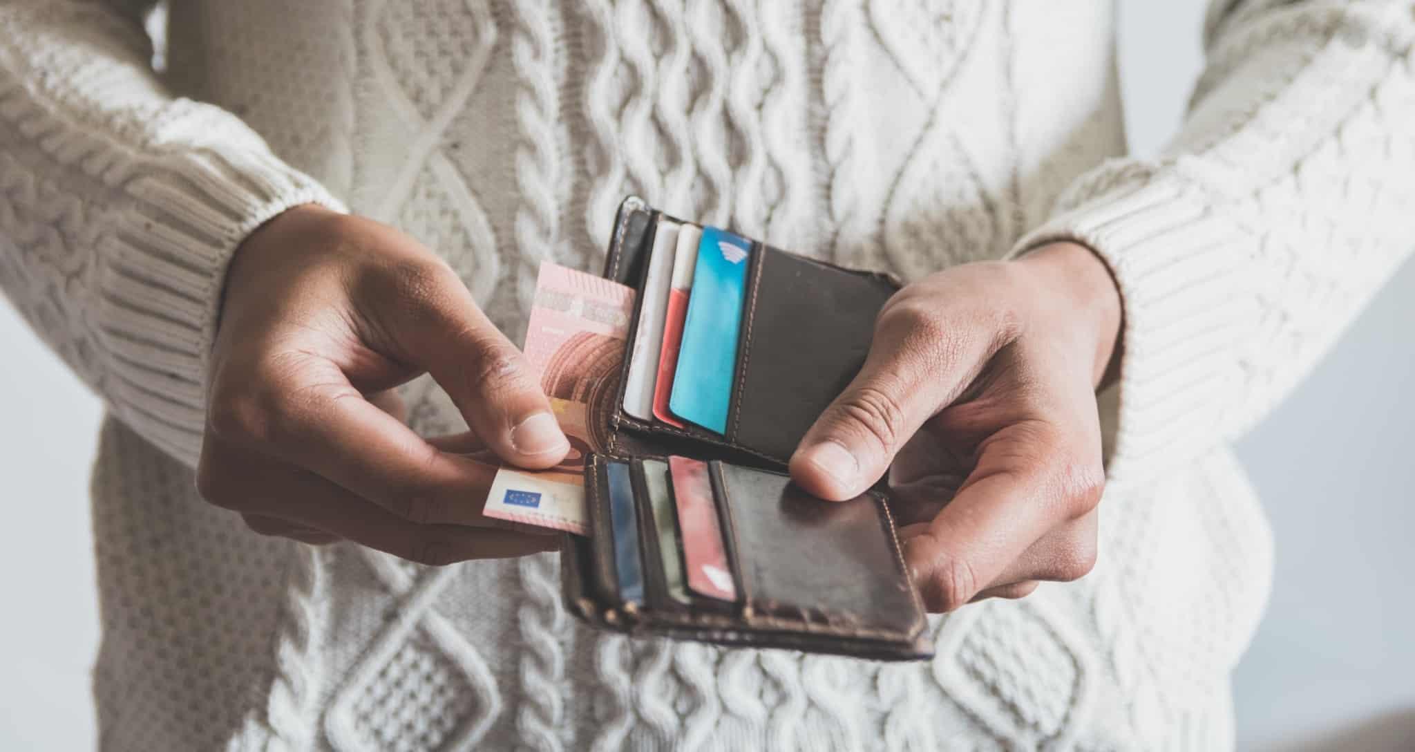 Pessoa a tirar uma nota de 10 euros de uma carteira com cartões de crédito