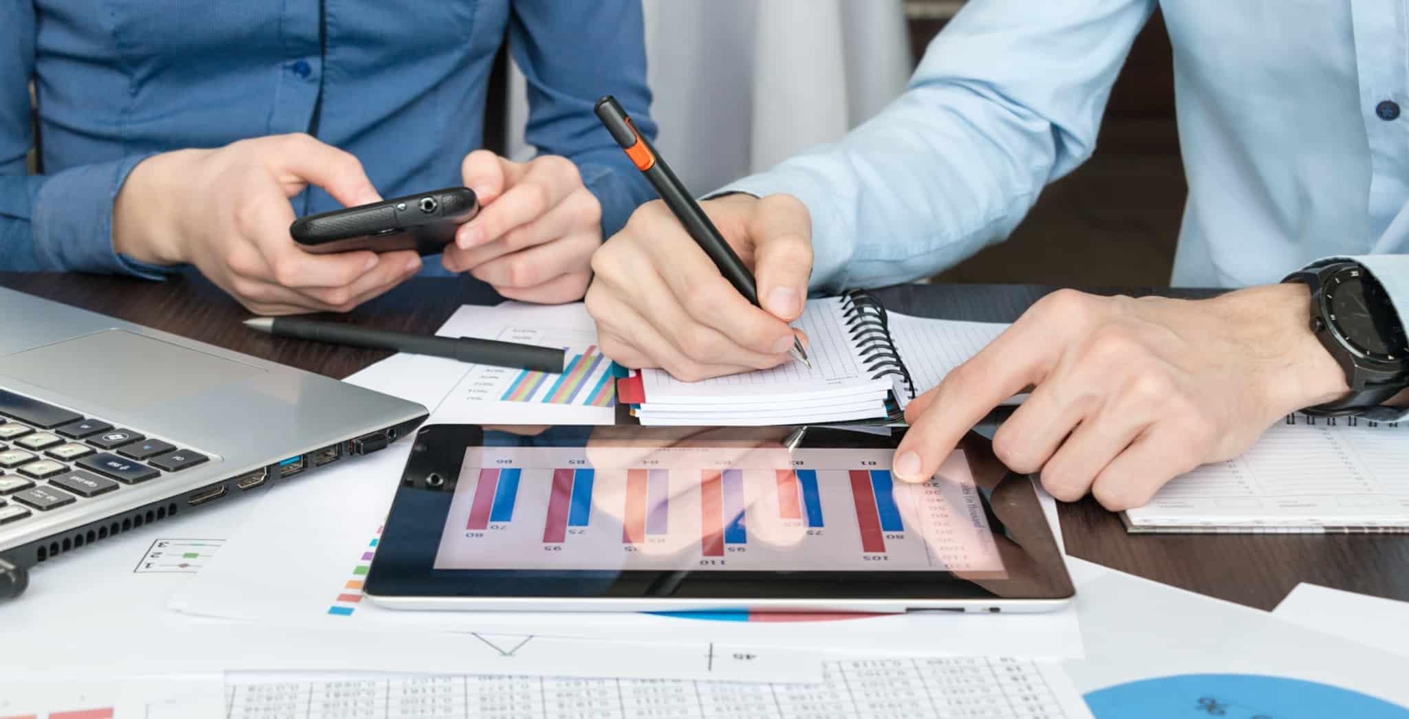 Dois empresários a verificar aplicações financeiras e a fazer contas