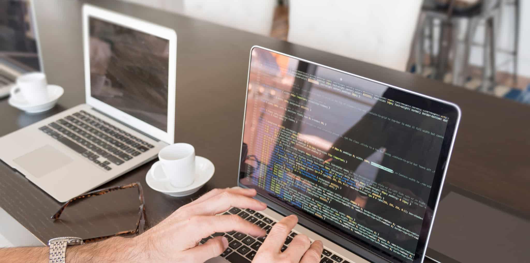 Homem a escrever no computador com chavena de café