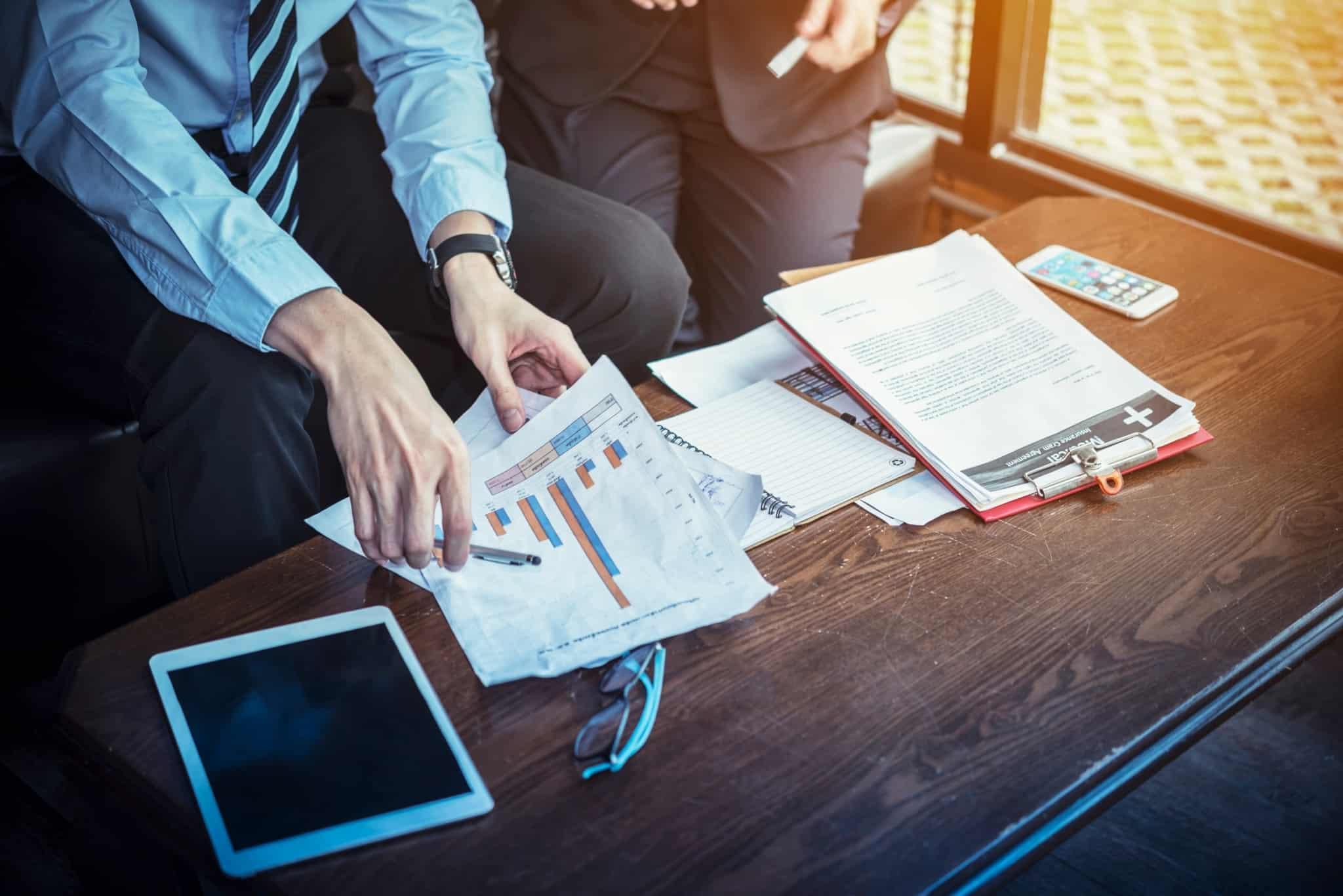dois profissionais analisam folhas com gráficos com um tablet em cima de uma mesa