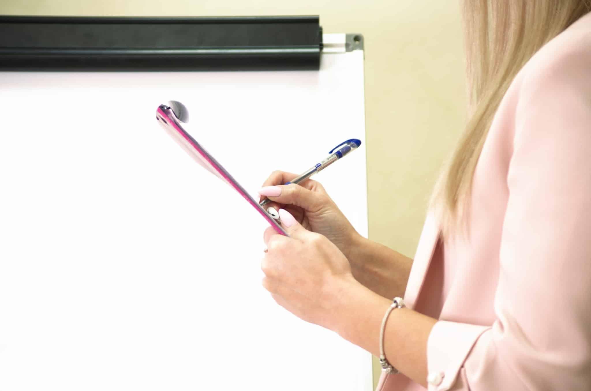 mulher de blazer cor de rosa a tirar notas