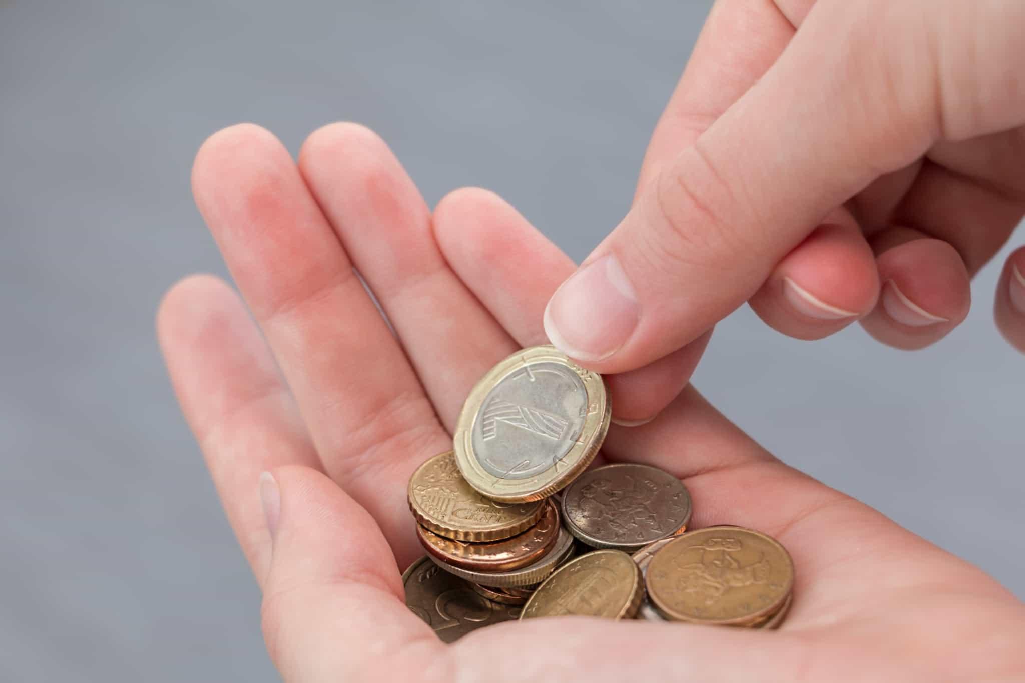 moedas de euros na mão de uma pessoa