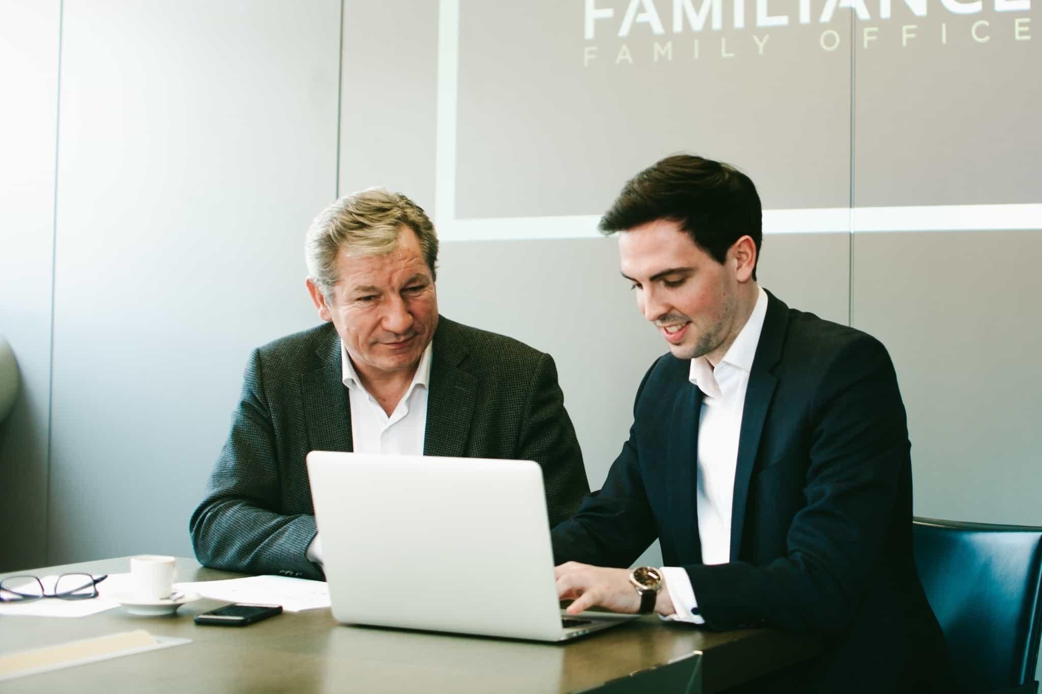 dois empresários com um portátil à frente