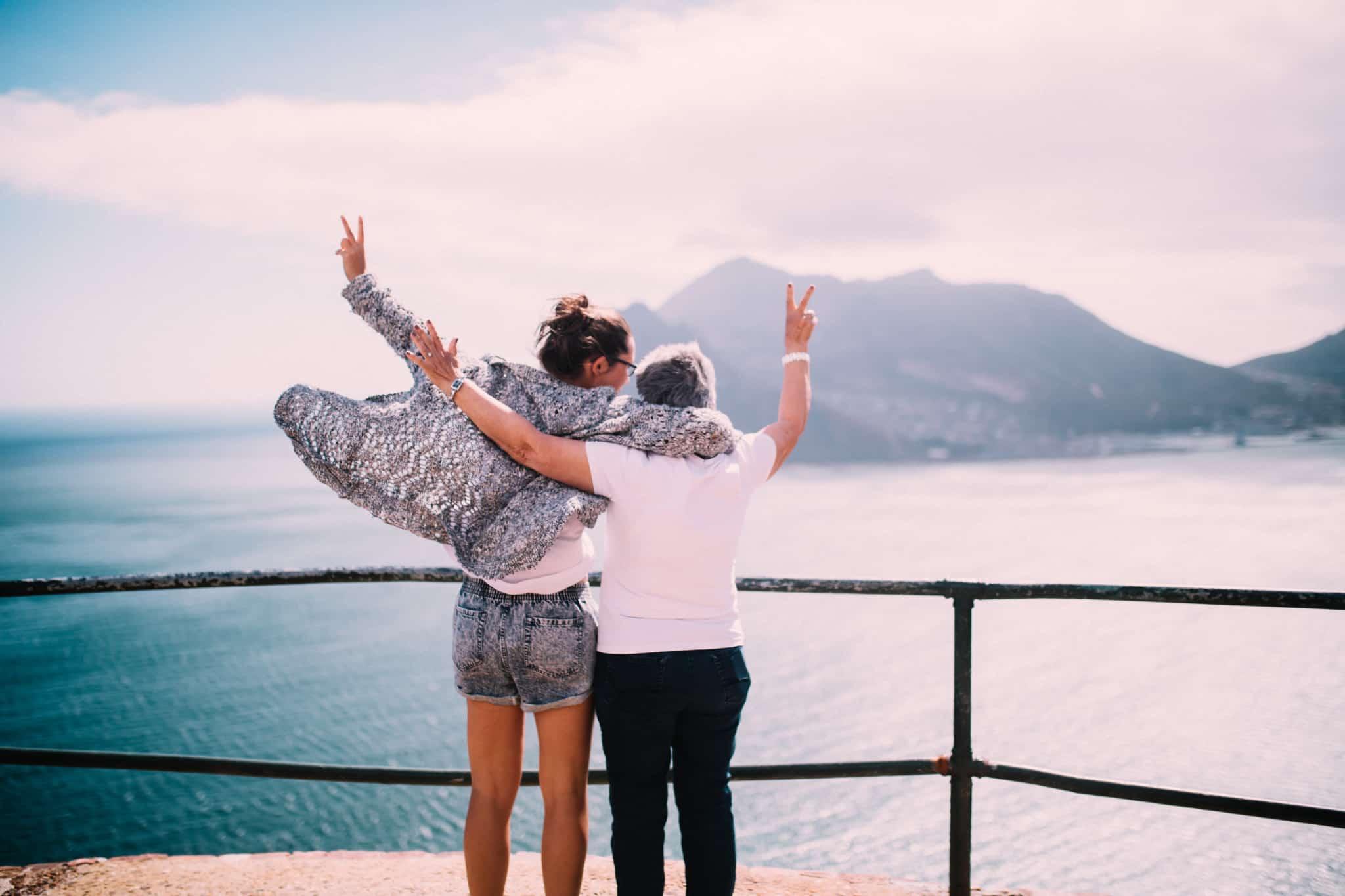 jovem com a mãe contentes a olhar para uma montanha