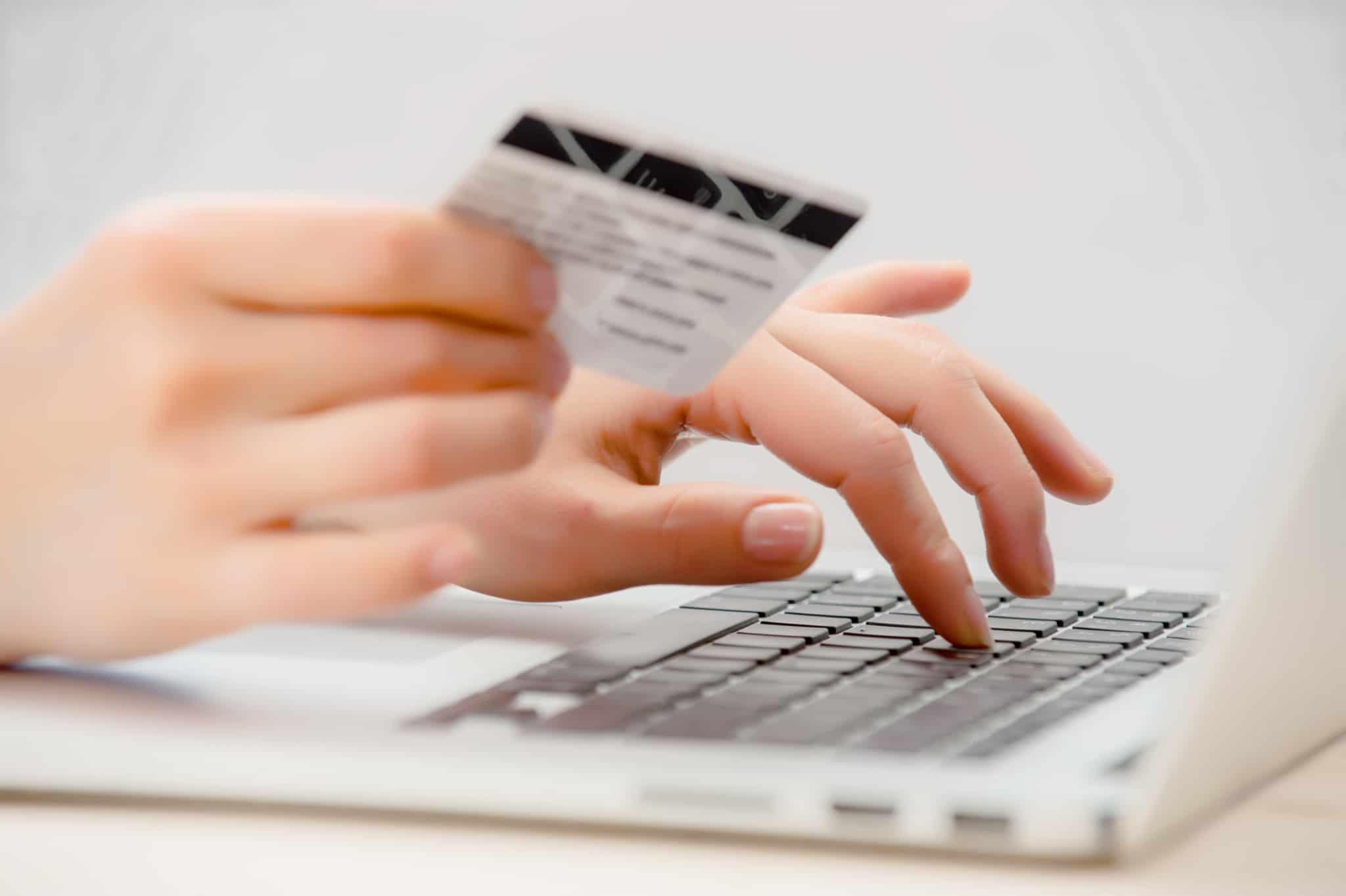 pessoa a fazer compras online a segurar cartão