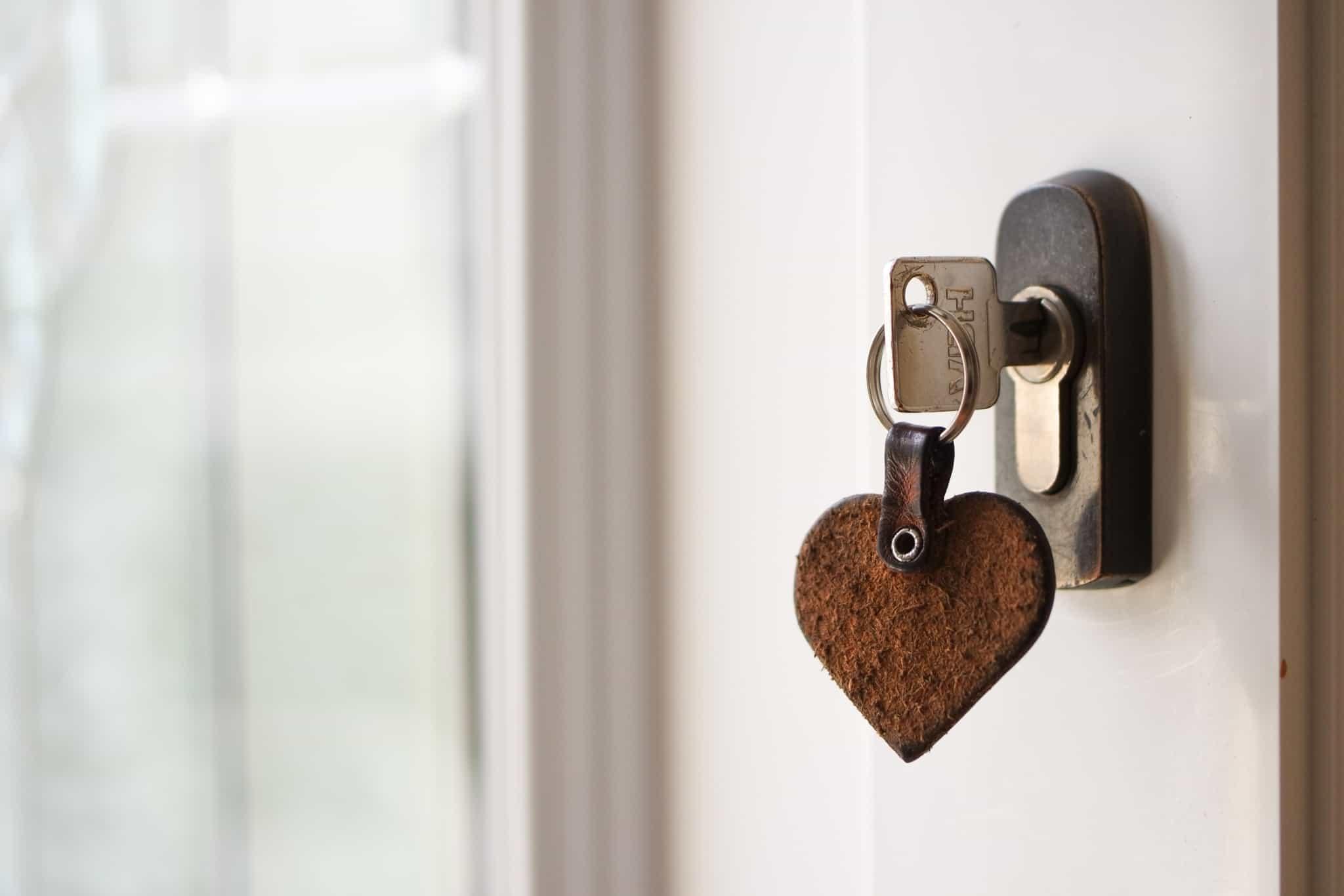 chave de casa colocada na fechadura com um porta chaves de um coraçao