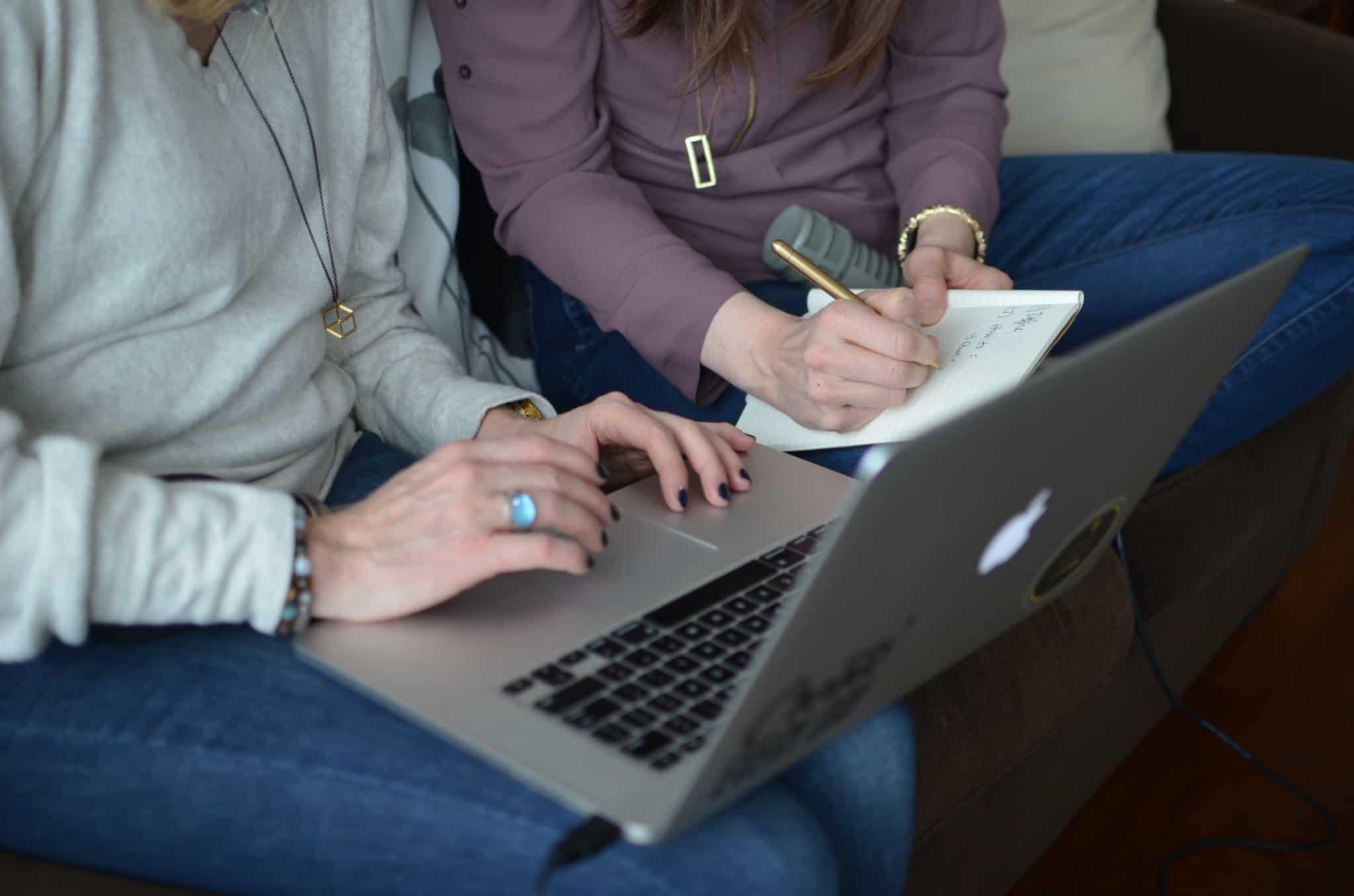 duas mulheres uma com computador e outra com bloco e caneta a trabalhar