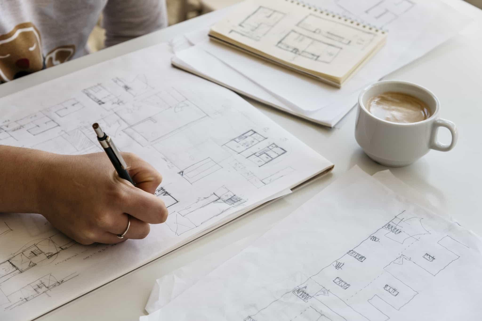 arquitecta a fazer projeto com chavena de cafe