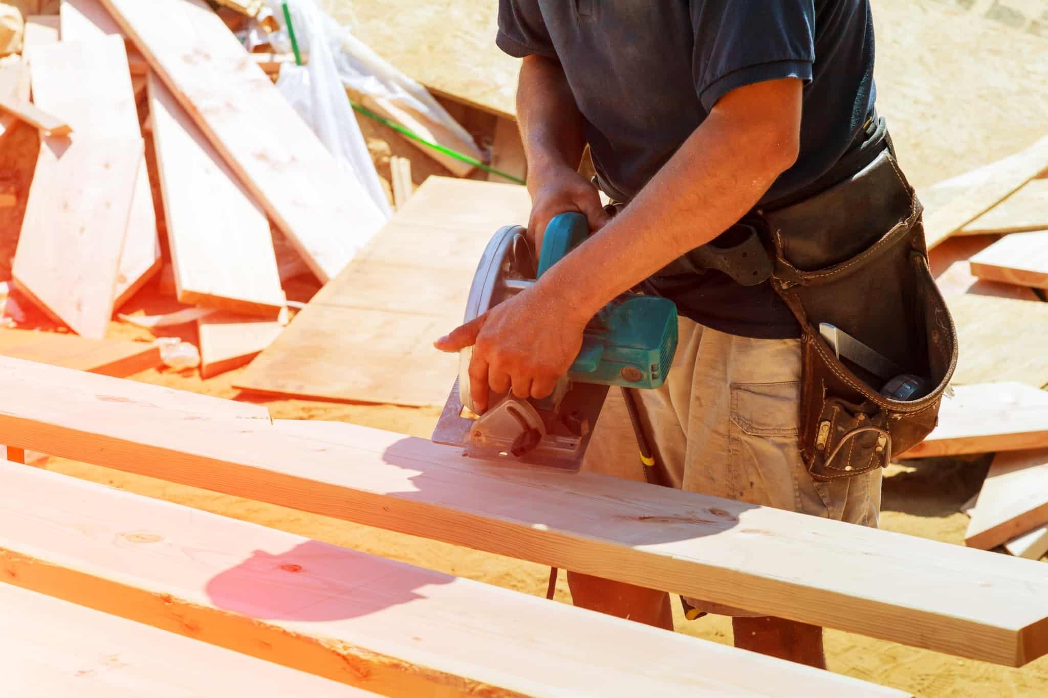 construtor a cortar tabuas de madeira com ferramenta