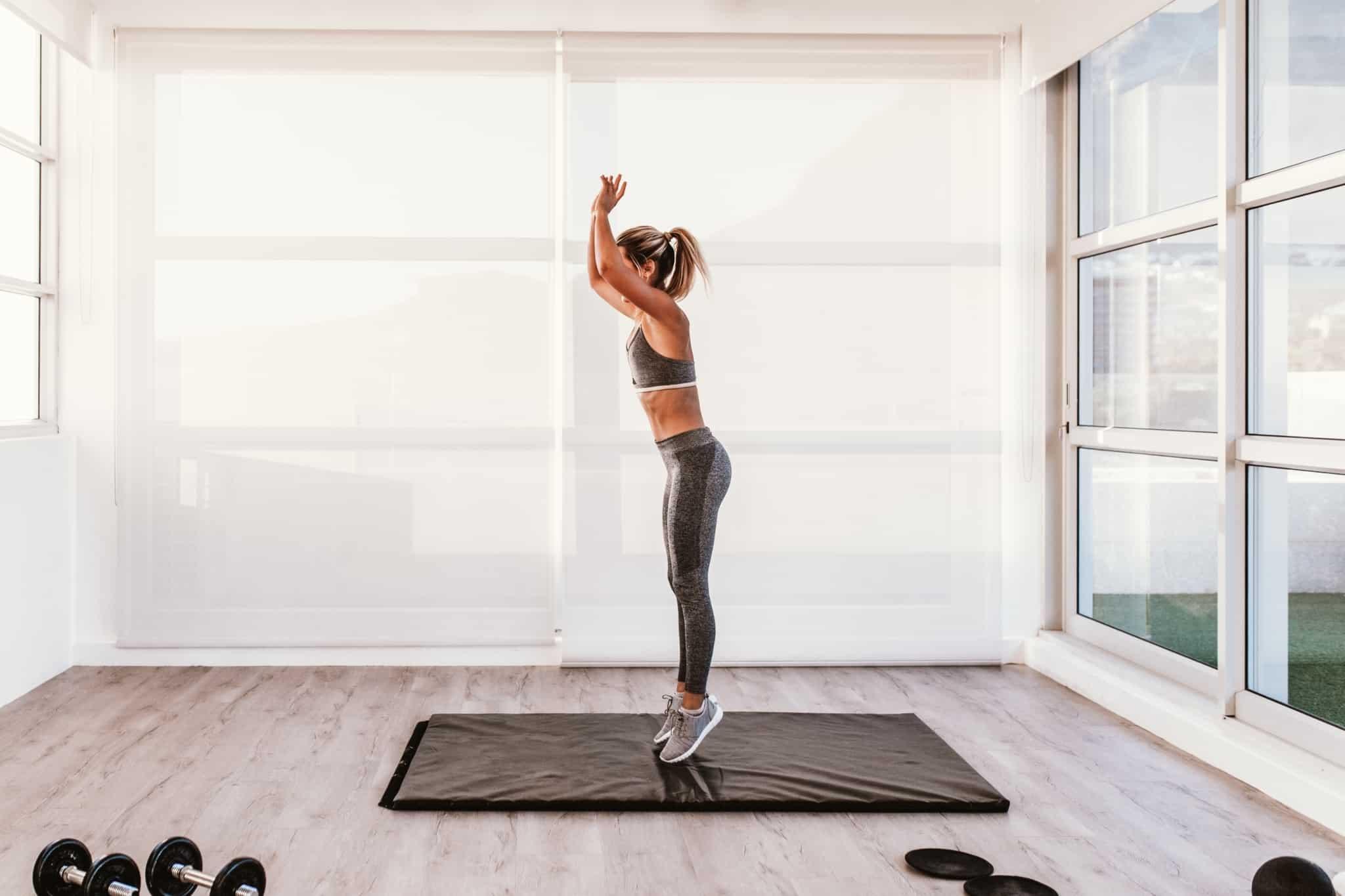 rapariga de fato de treino a treinar em casa em cima de um colchao cinzento