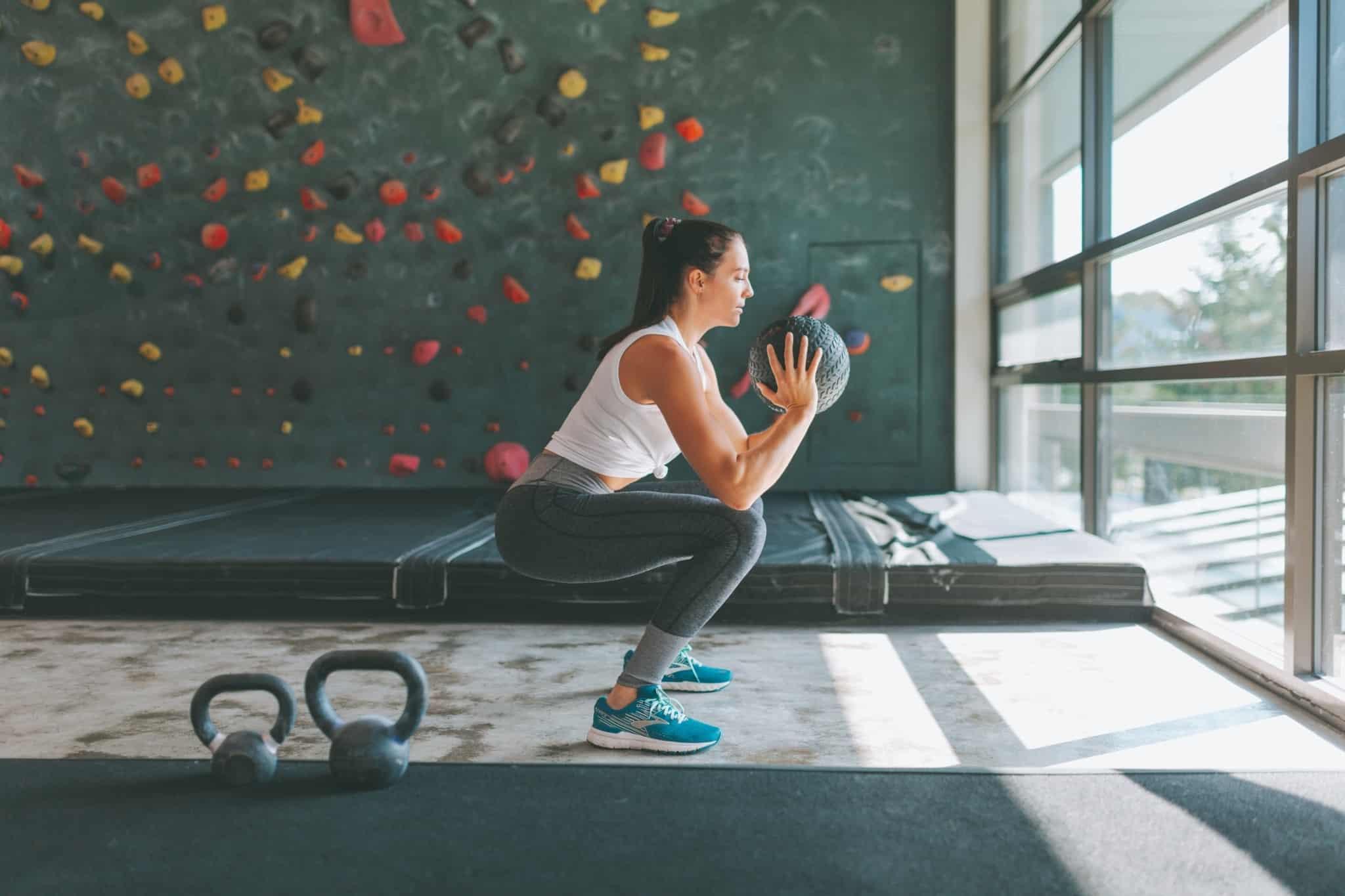 mulher a treinar num ginasio, a fazer um agachamento com a bola nas mãos