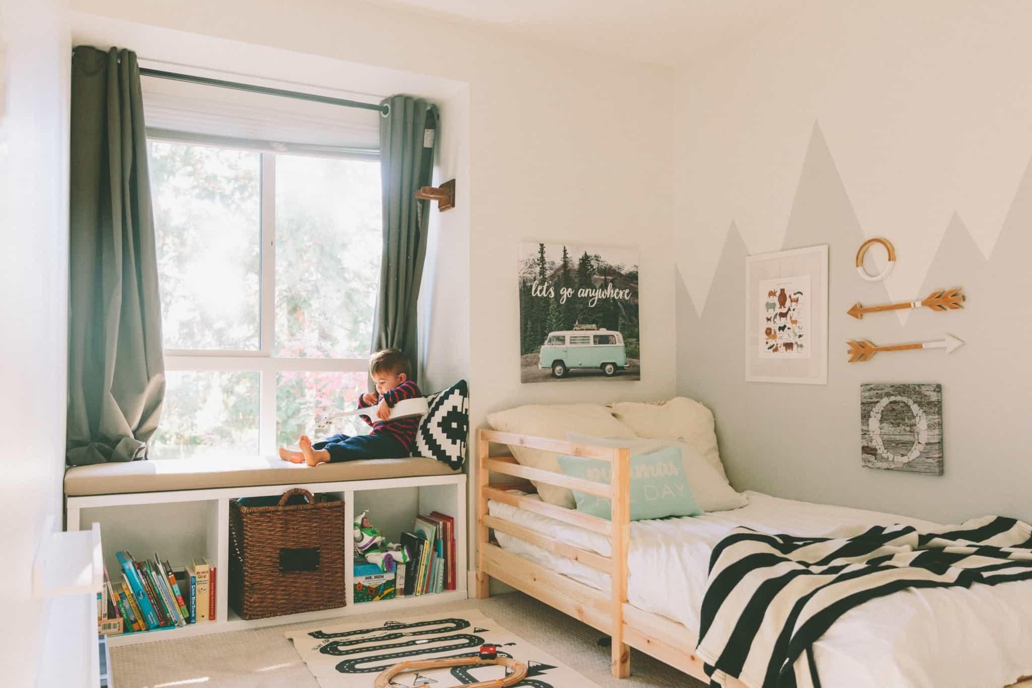 rapaz brinca no seu quarto perto da janela