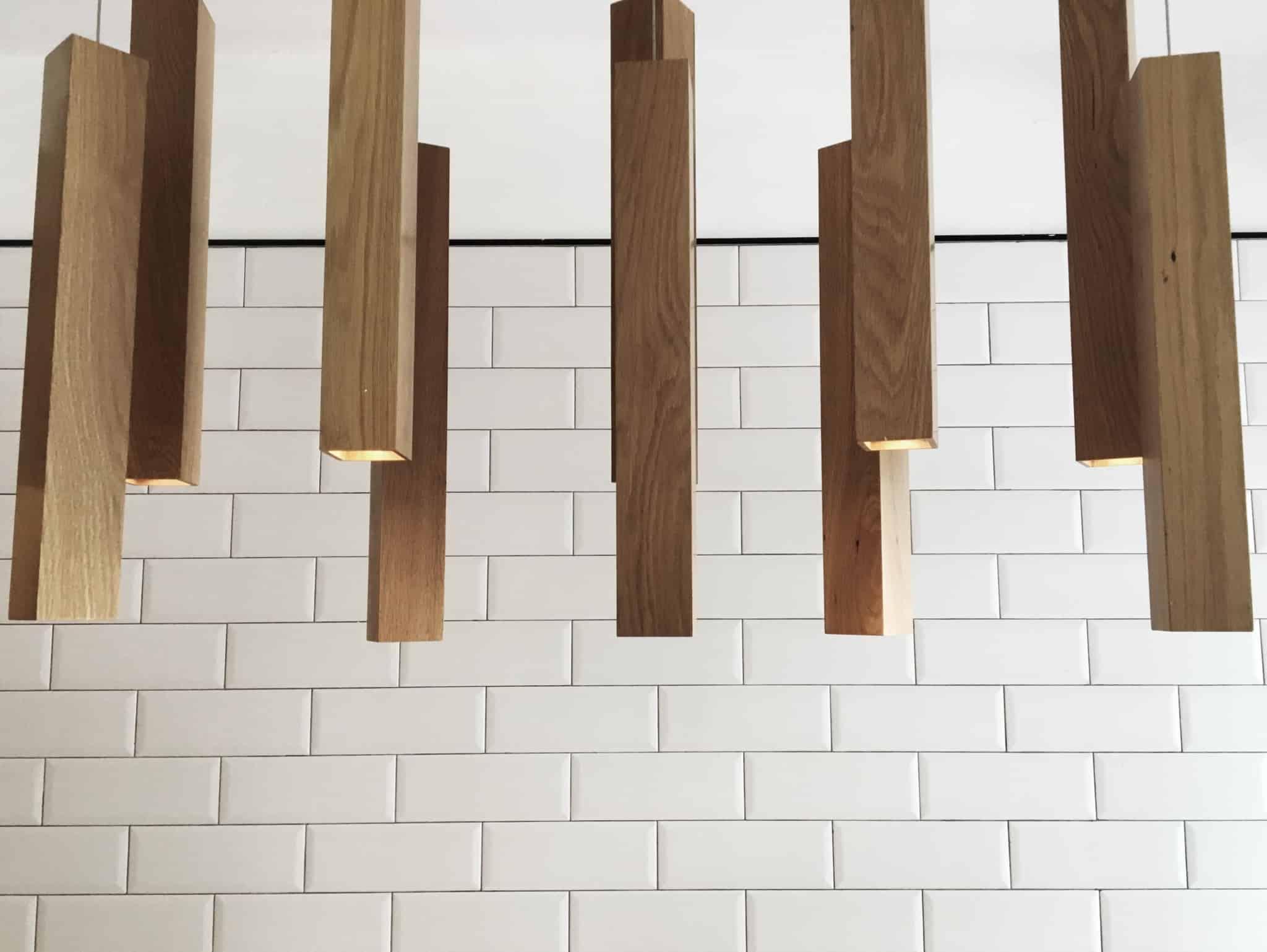 parede com tijolos brancos e estacas de madeira penduradas no tecto