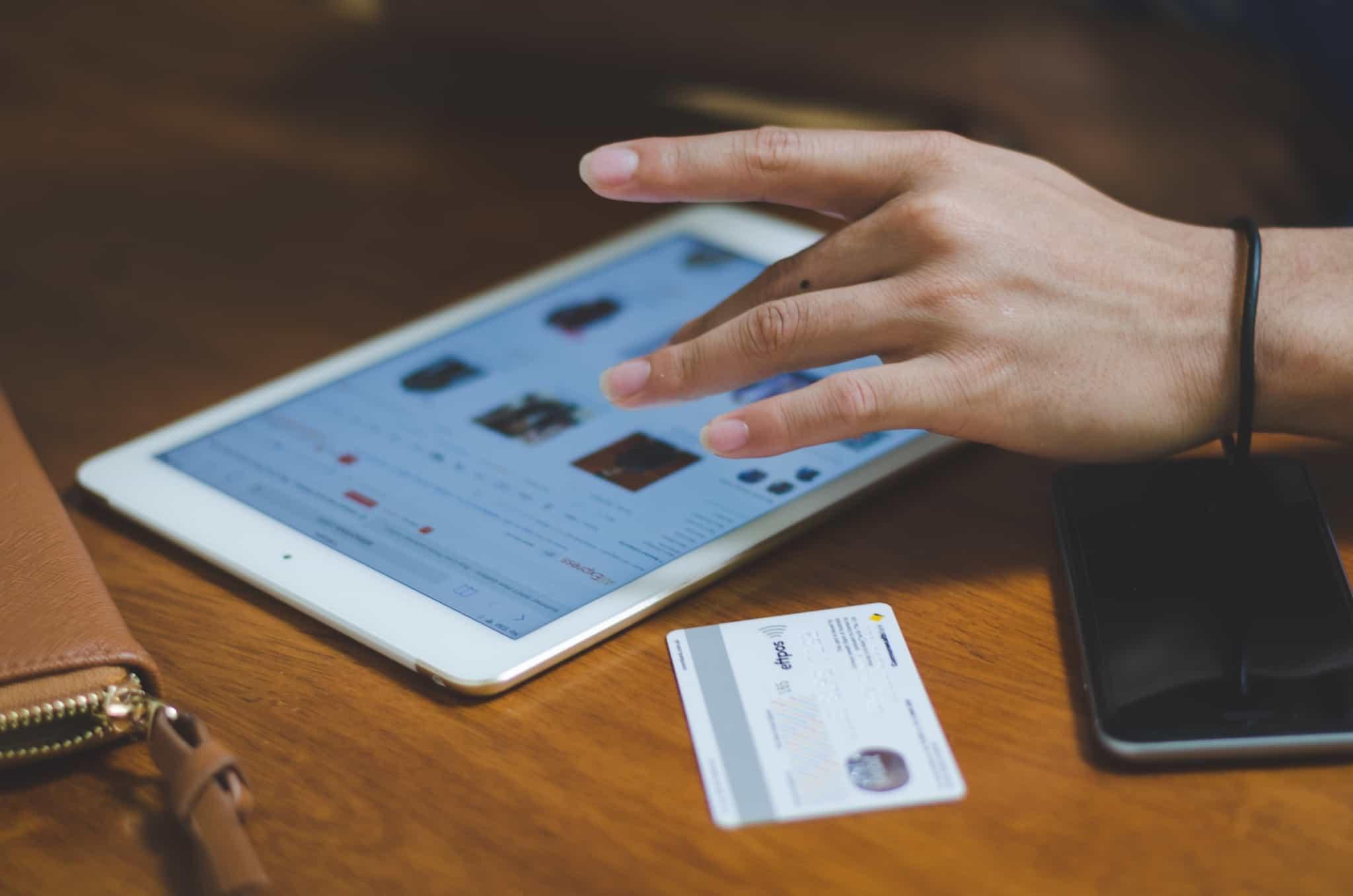 pessoa a fazer compras online no tablet com o cartão ao lado