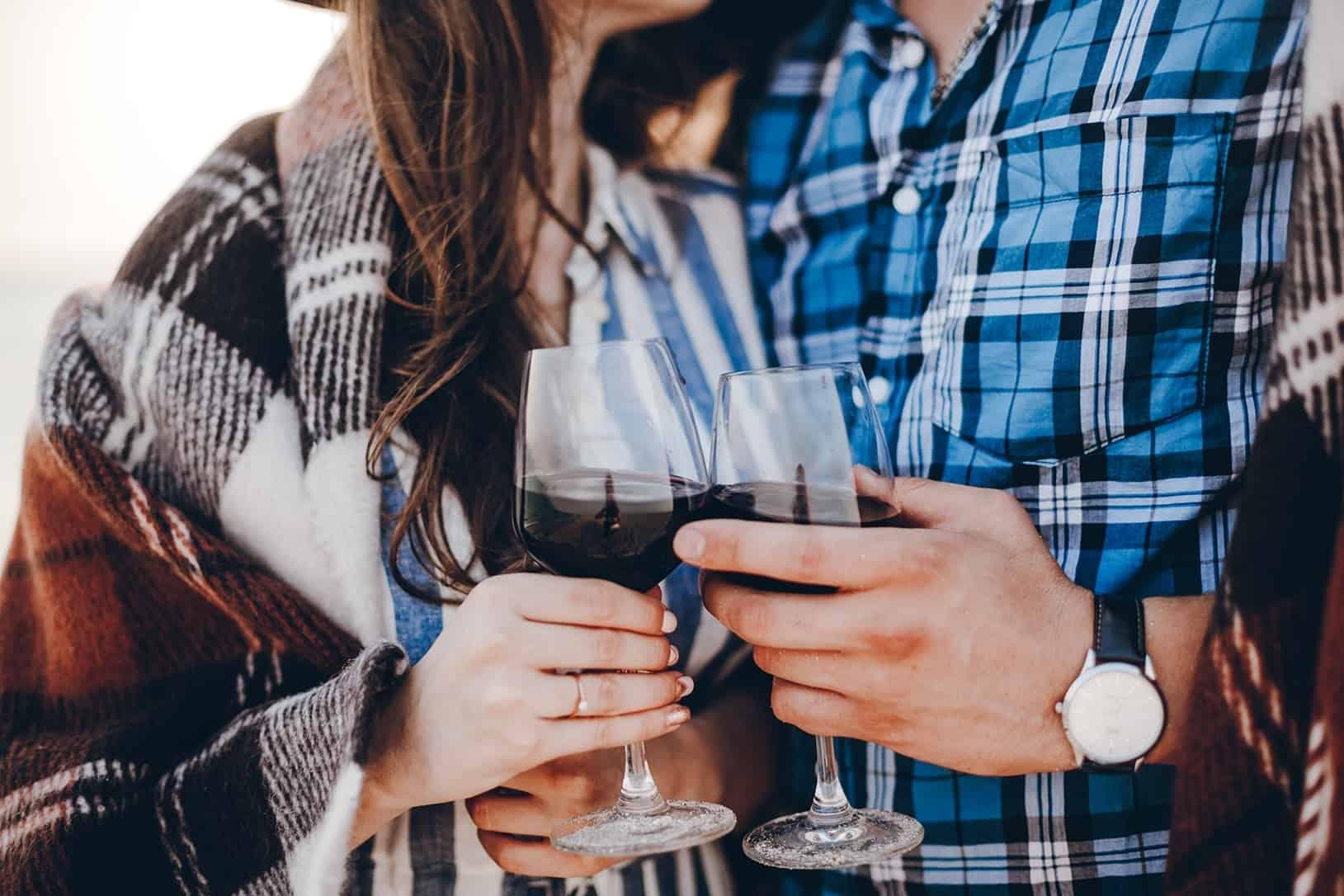 casal a fazer brinde com copo de vinho