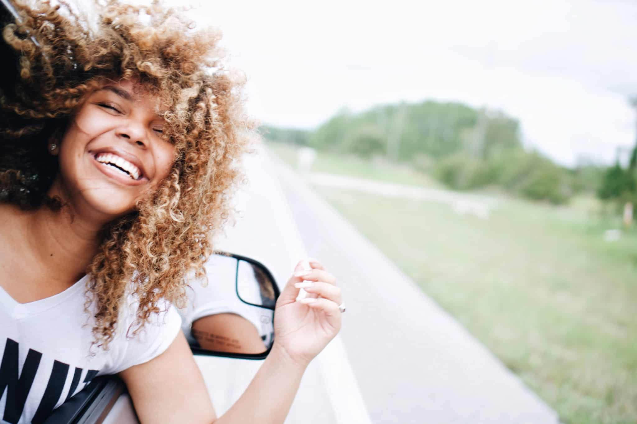 rapariga com cabelo ao vento na janela do carro