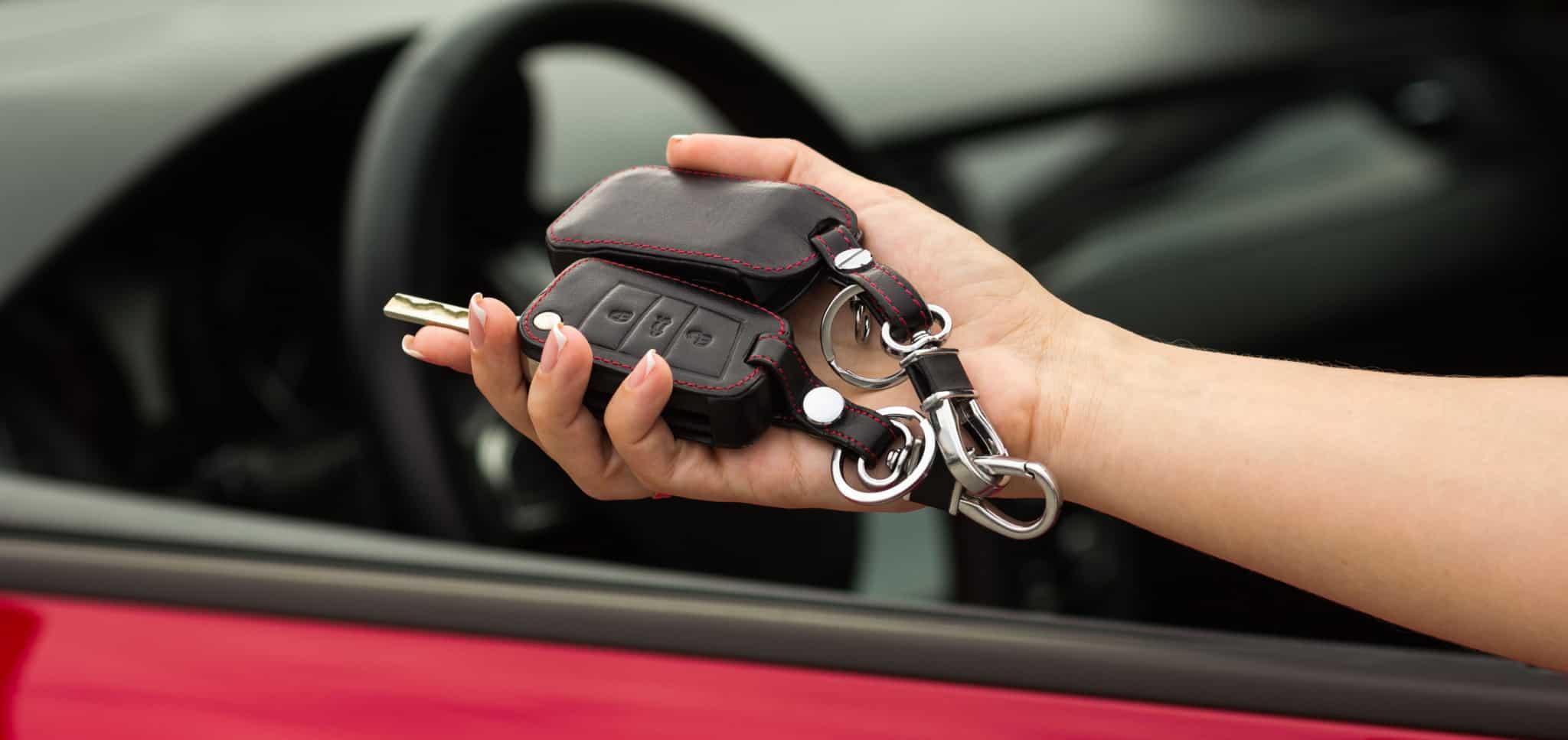 Mulher a pegar em chaves de um carro vermelho