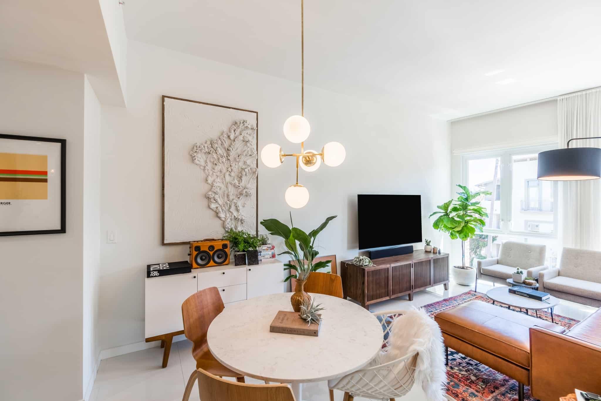 sala de estar com televisão sofã e mesa redonda com 4 cadeiras