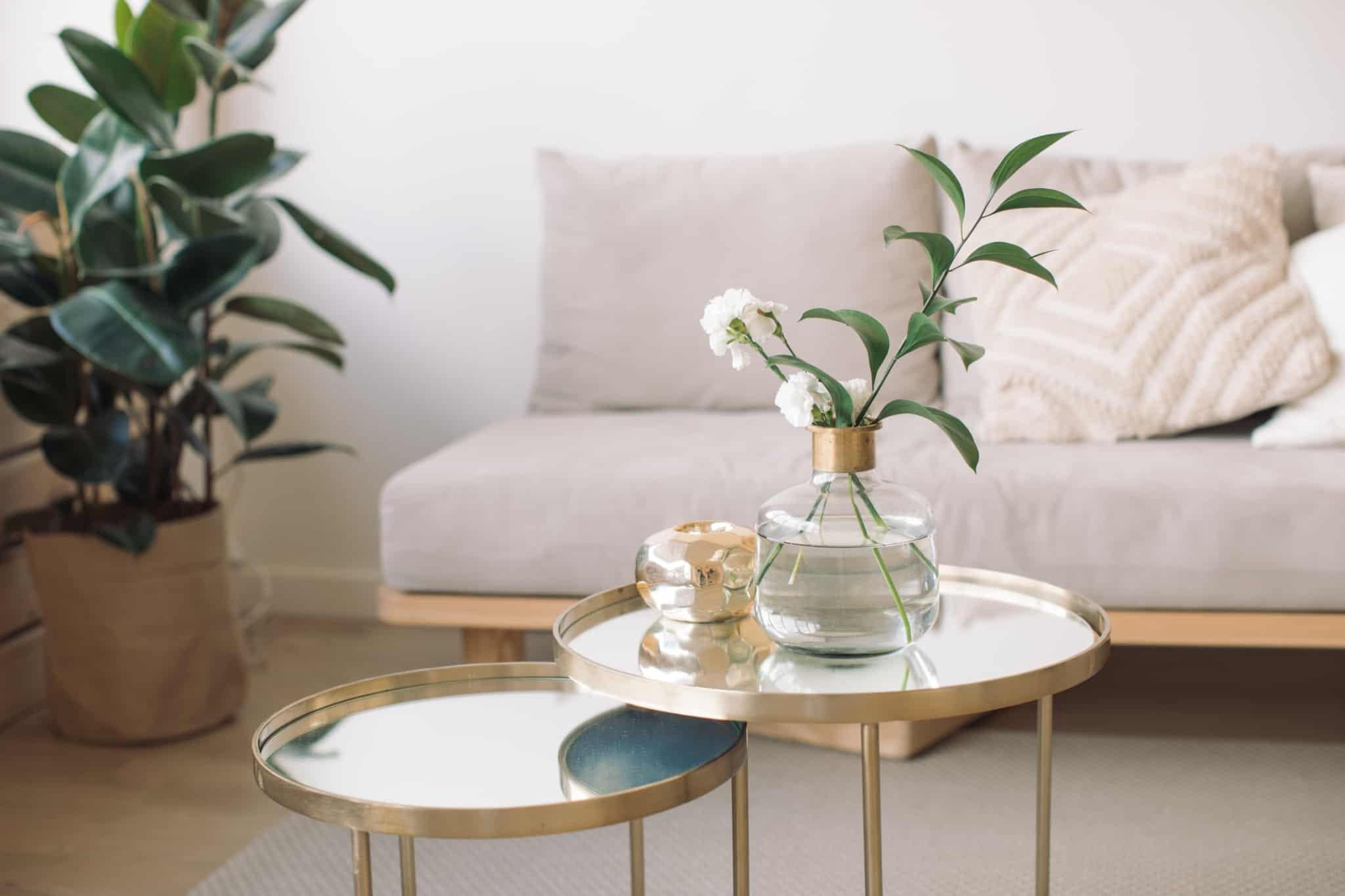 mesa de apoio em sala com flores e sofa creme