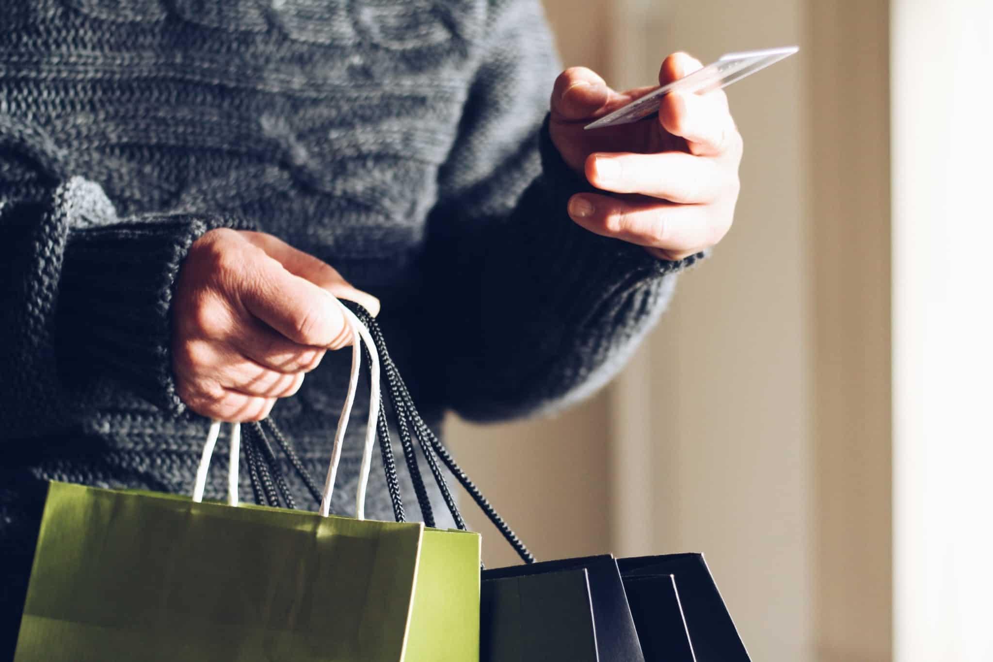 pessoa com sacos de compras e a mostrar cartao de credito