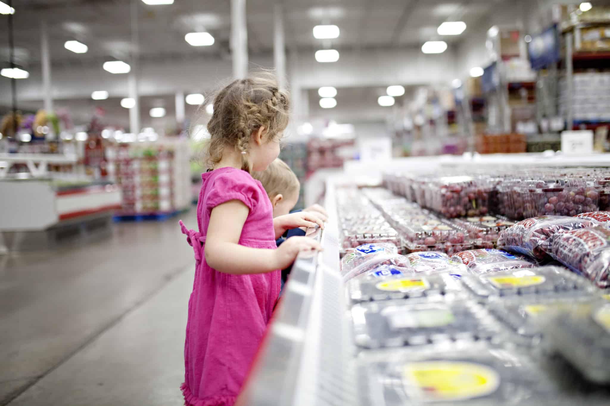 crianças a escolher fruta no supermercado