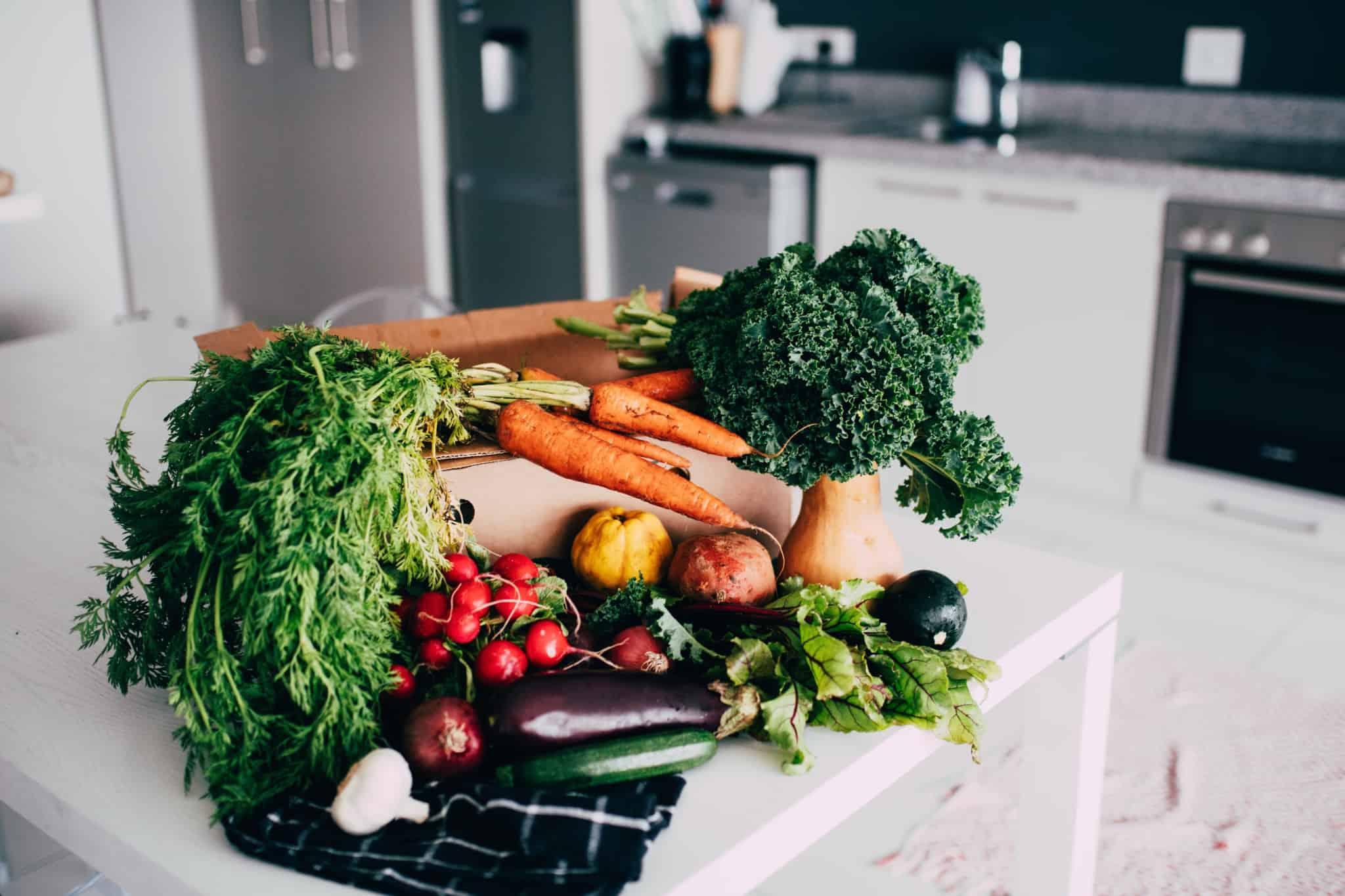 legumes dentro de uma caixa de cartão na bancada da cozinha