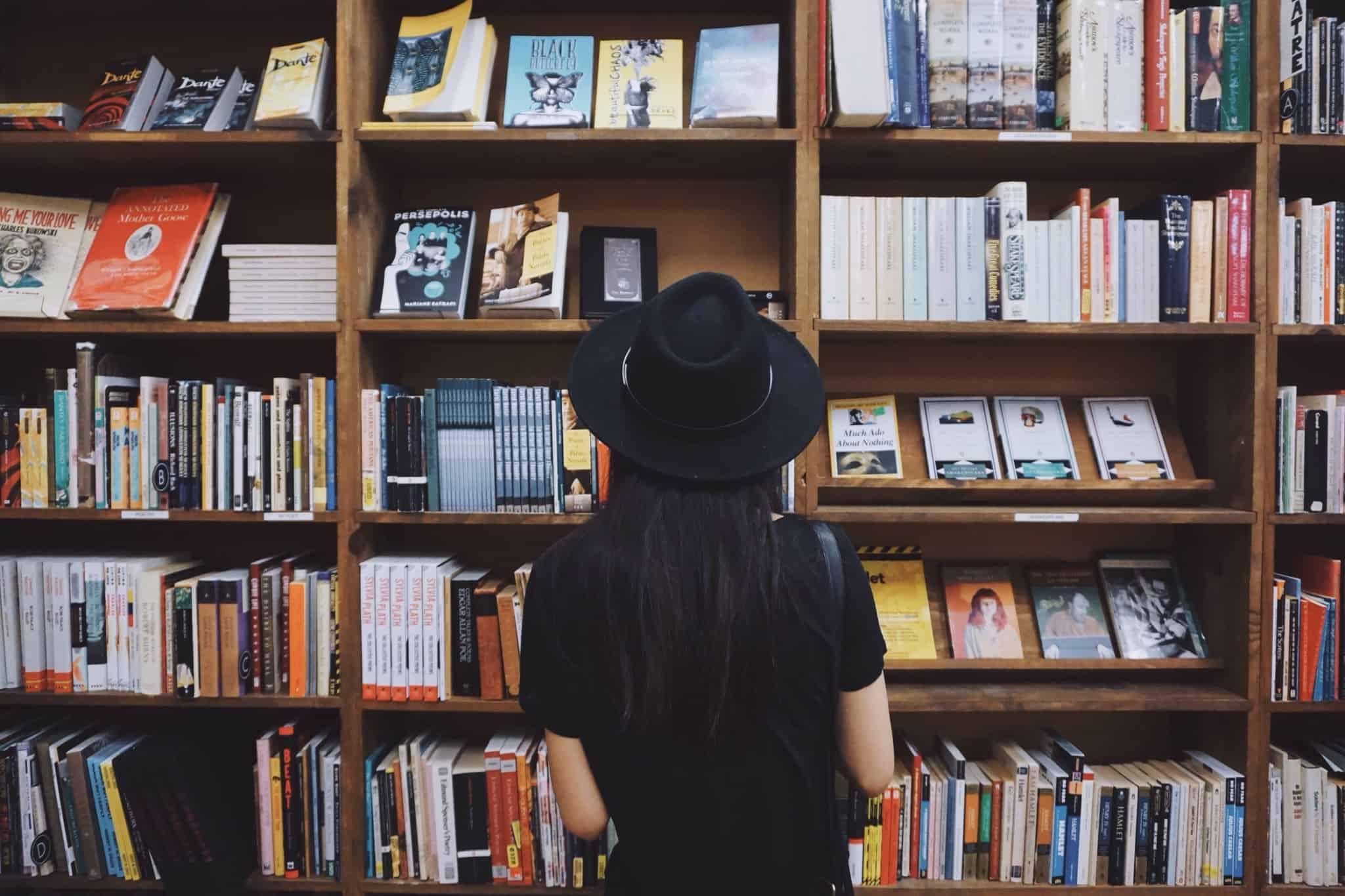 rapariga a olhar para estante de livros