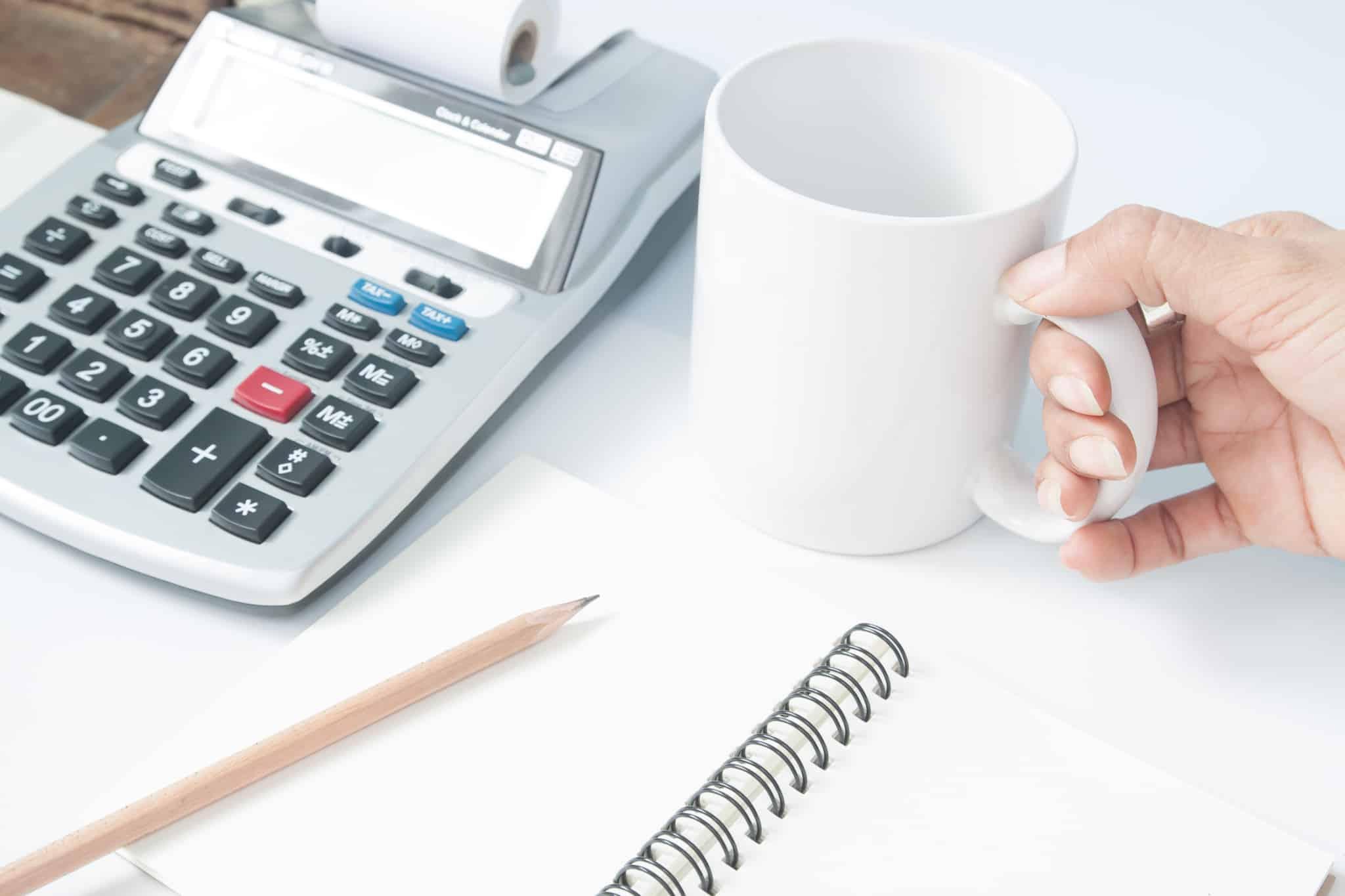 contabilista com bloco de notas chavena de cafe e calculadora