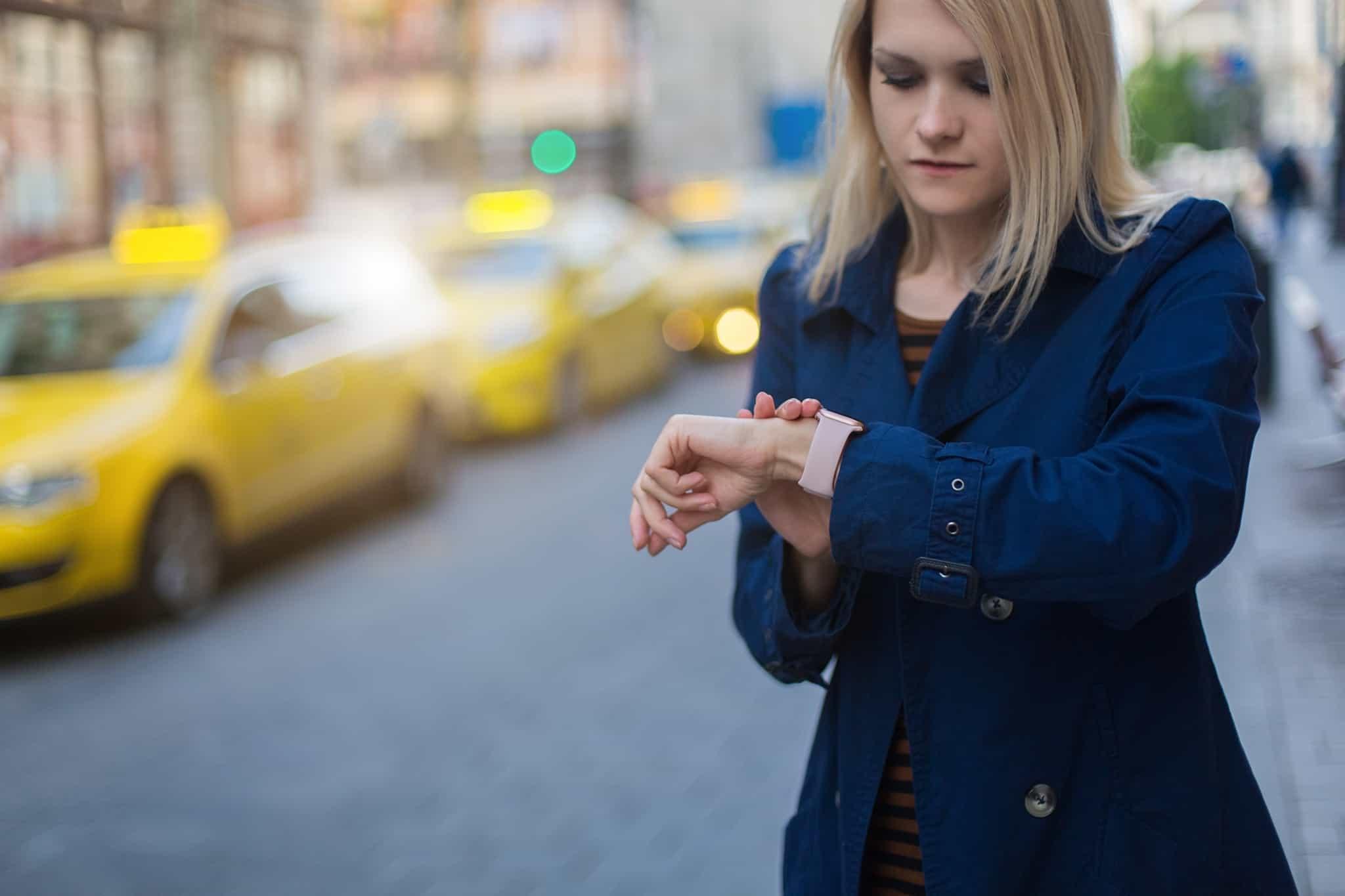 rapariga loira a olhar para o relogio a espera na estrada
