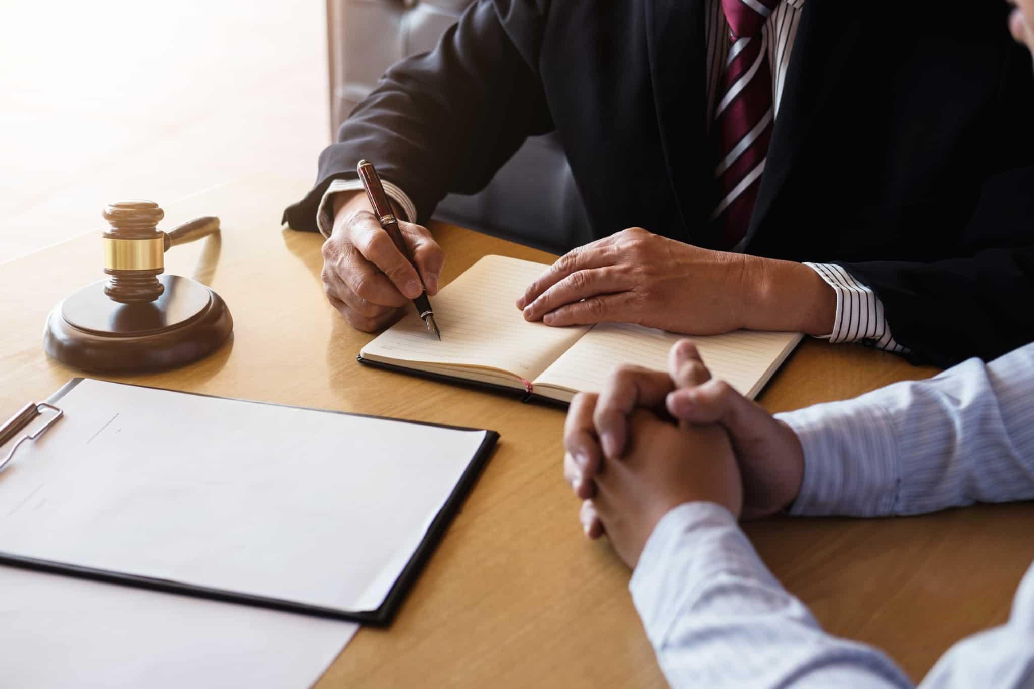 advogado a escrever em bloco de notas com o cliente ao lado