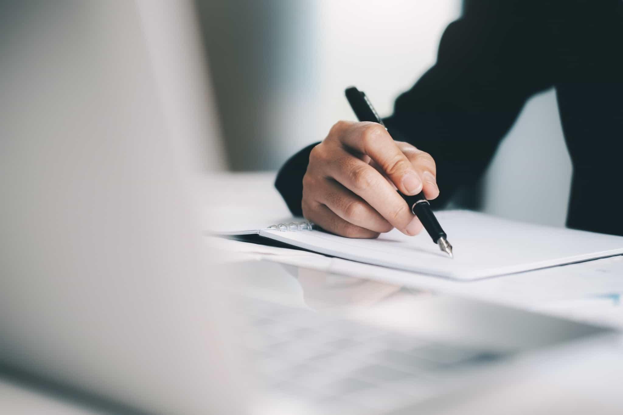pessoa a escrever com caneta preta profissional em papel