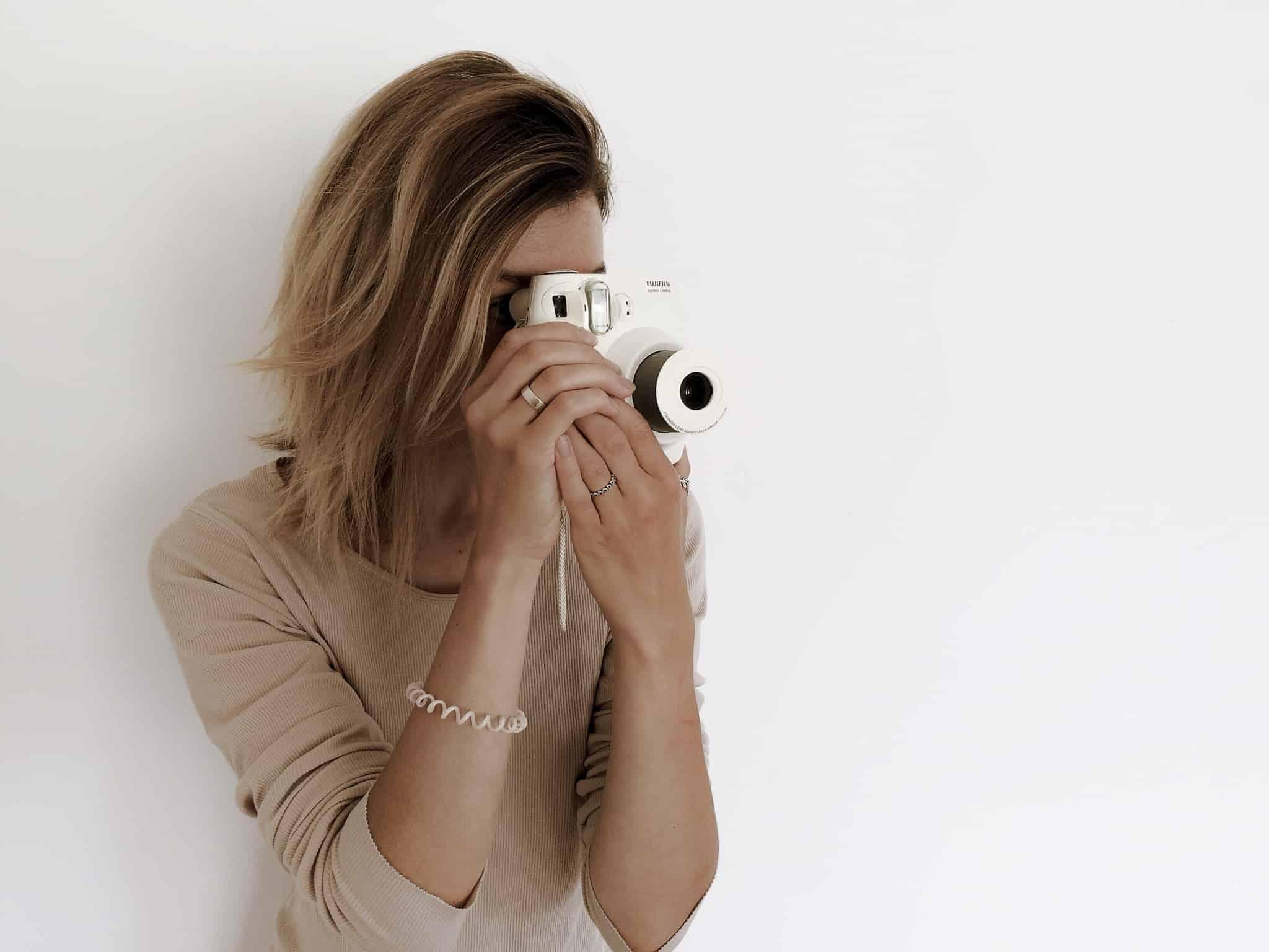 rapariga loira a tirar uma foto com camara branca