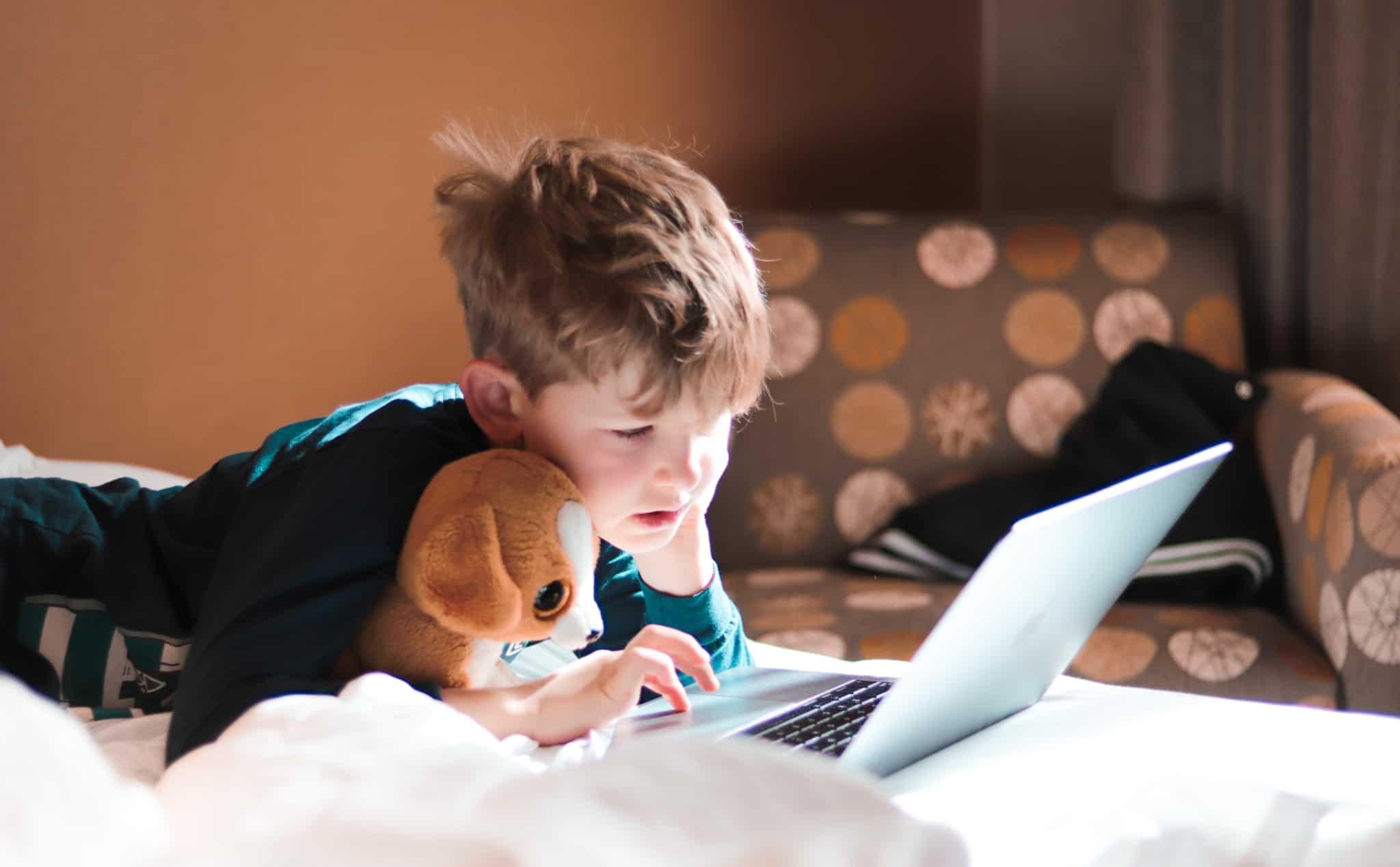 criança deitada na cama a mexer no portátil