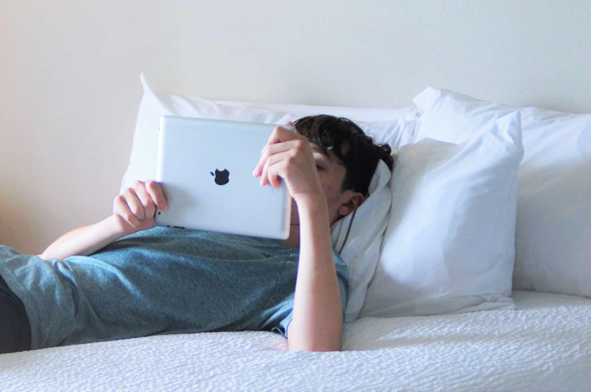 adolescente com um ipad na mao deitado na cama