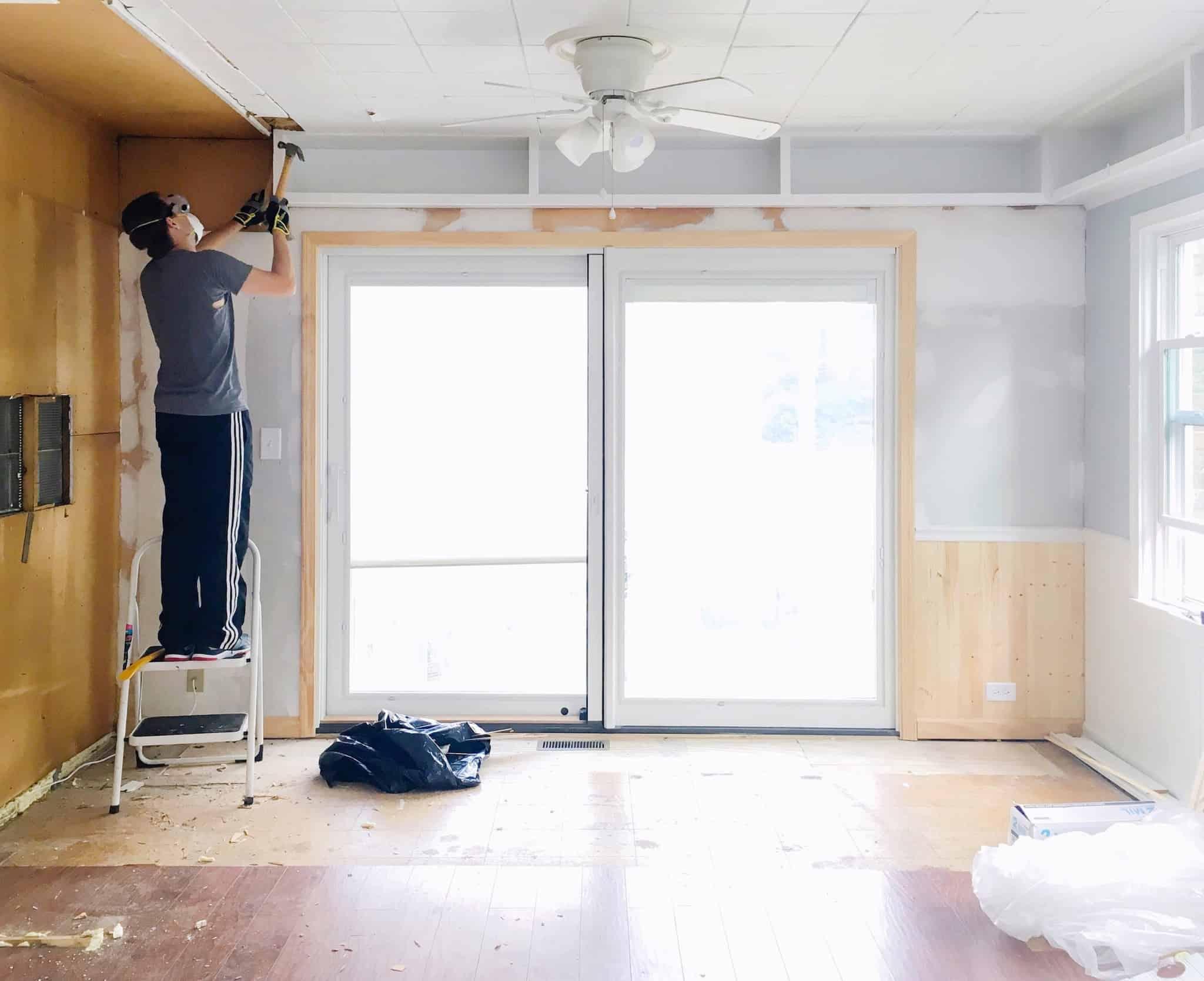 homem a fazer obras no tecto de uma sala