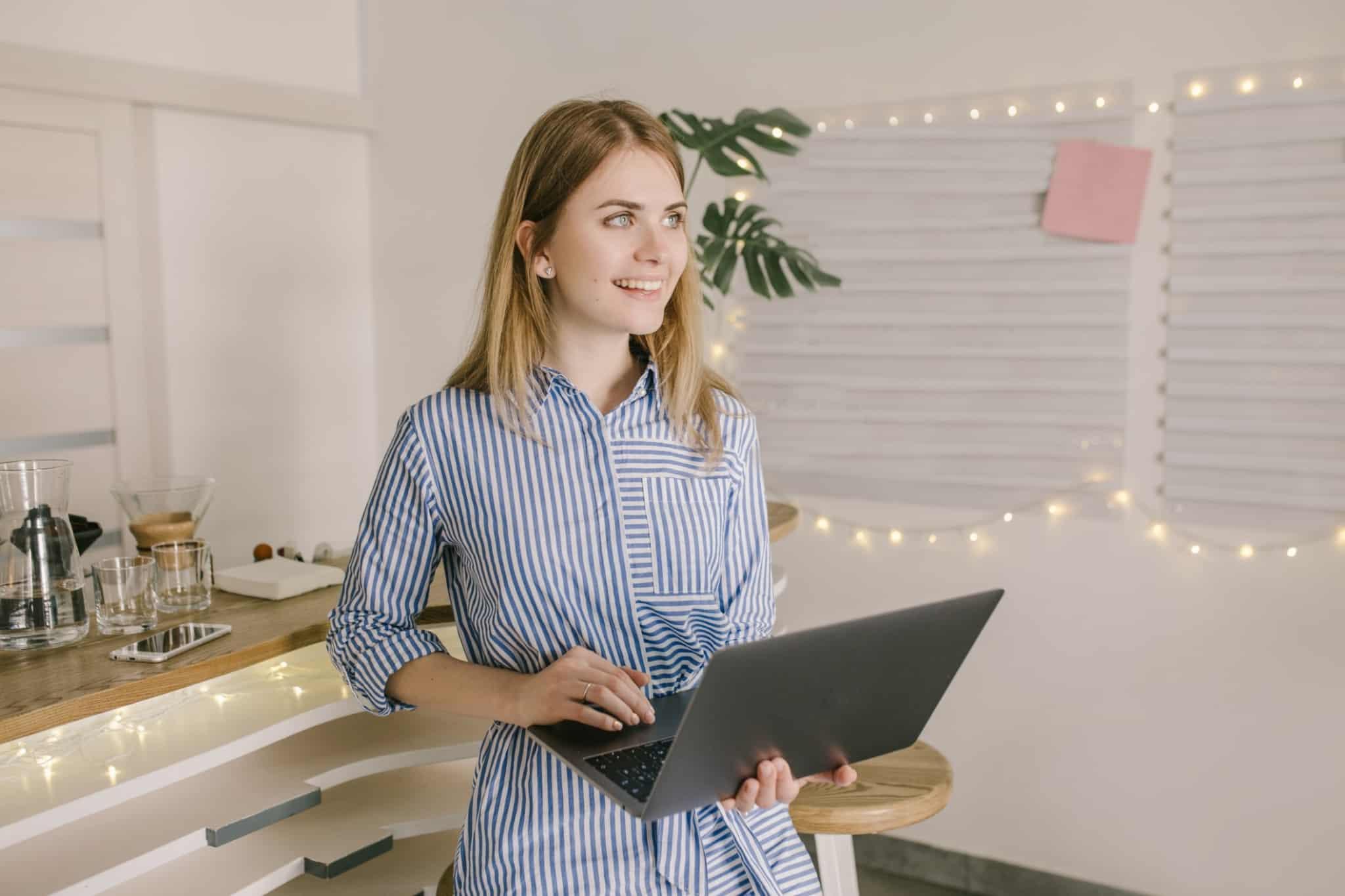 mulher loira sorridente a segurar o computador portatil na mao