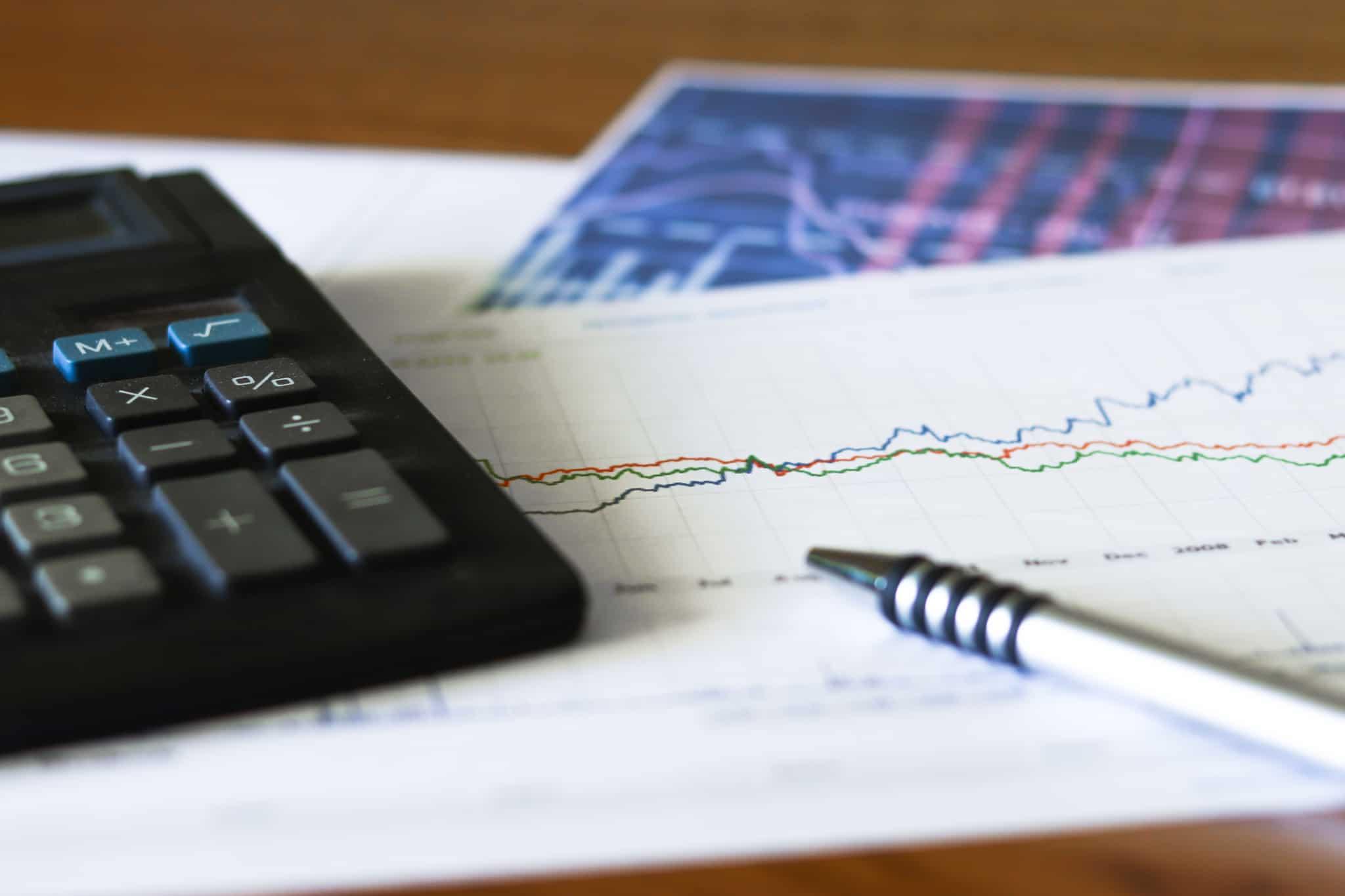 calculadora papel e caneta em cima da mesa