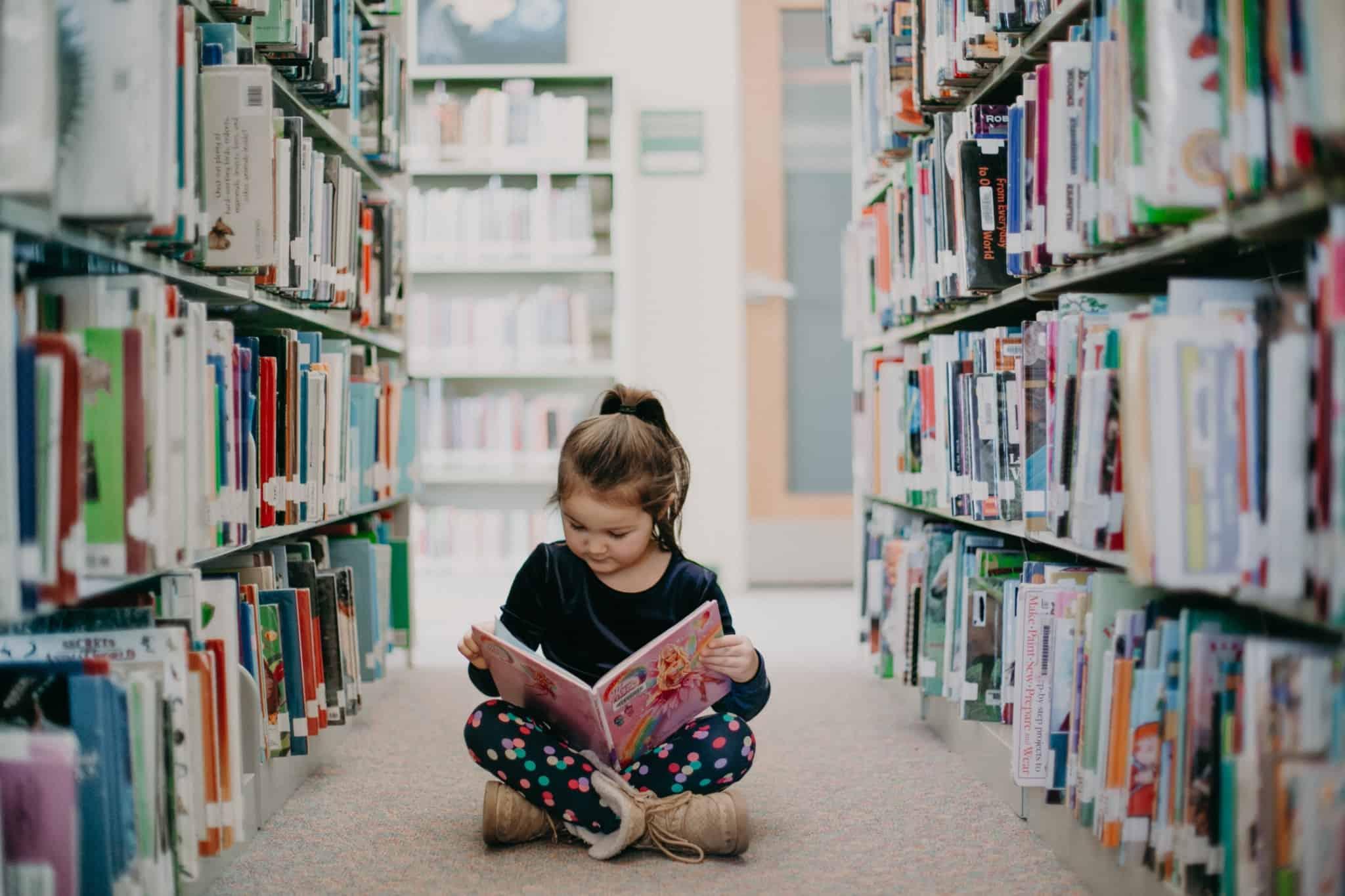 rapariga sentada no chão de uma biblioteca a ler um livro
