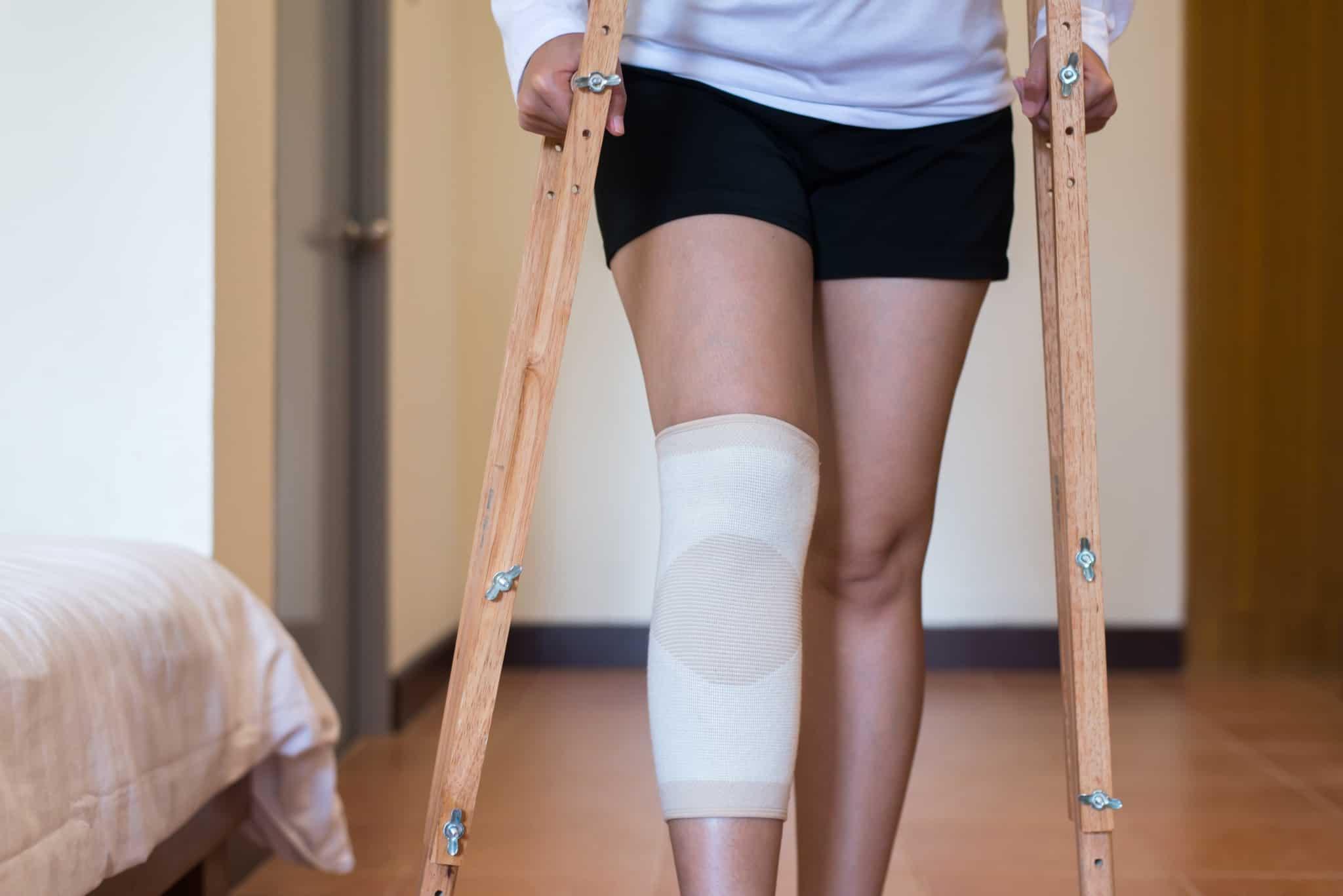 rapariga com um penso grande na perna e a andar de muletas de madeira