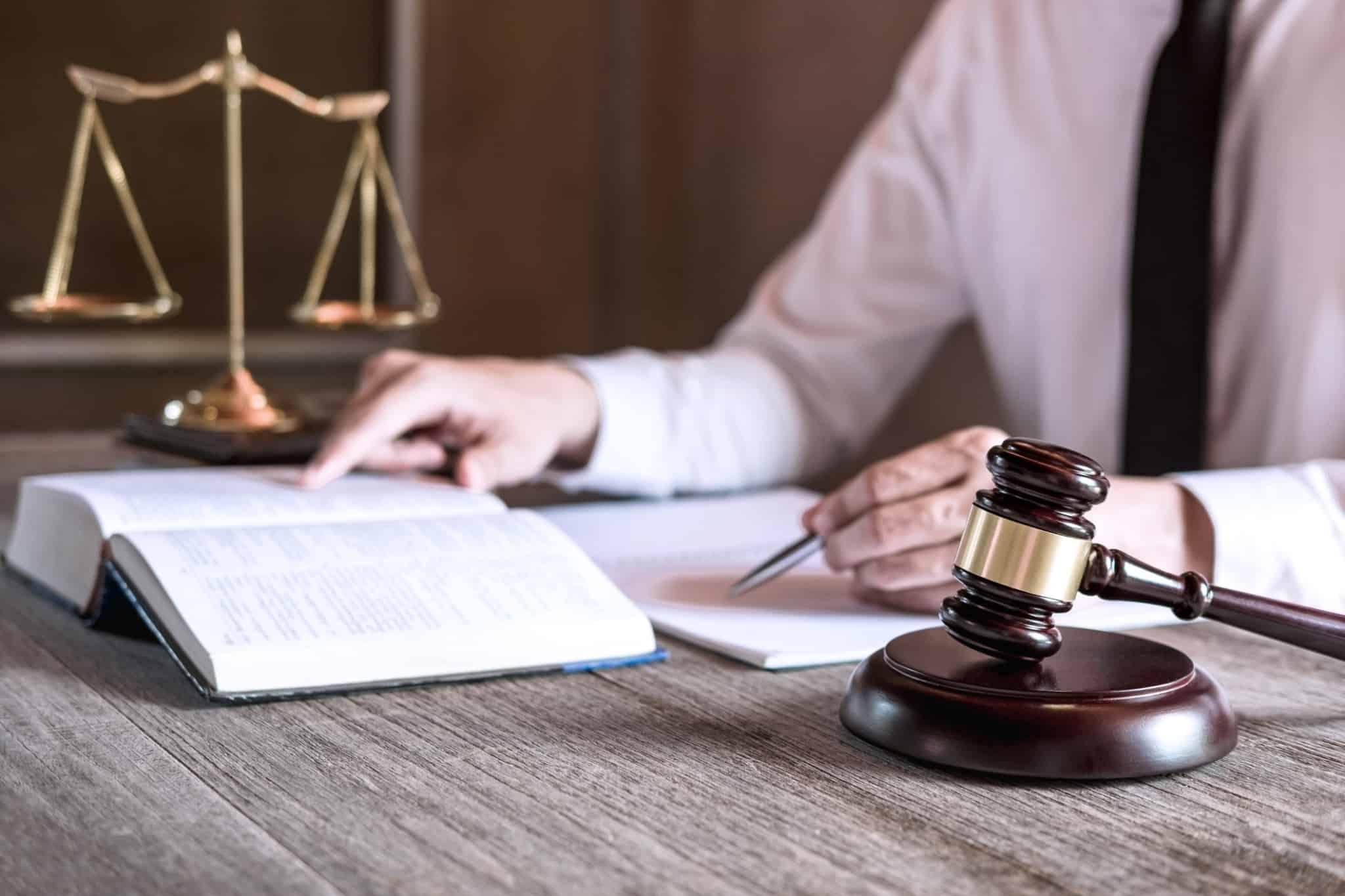 advogado a trabalhar num texto enquanto lê o código penal
