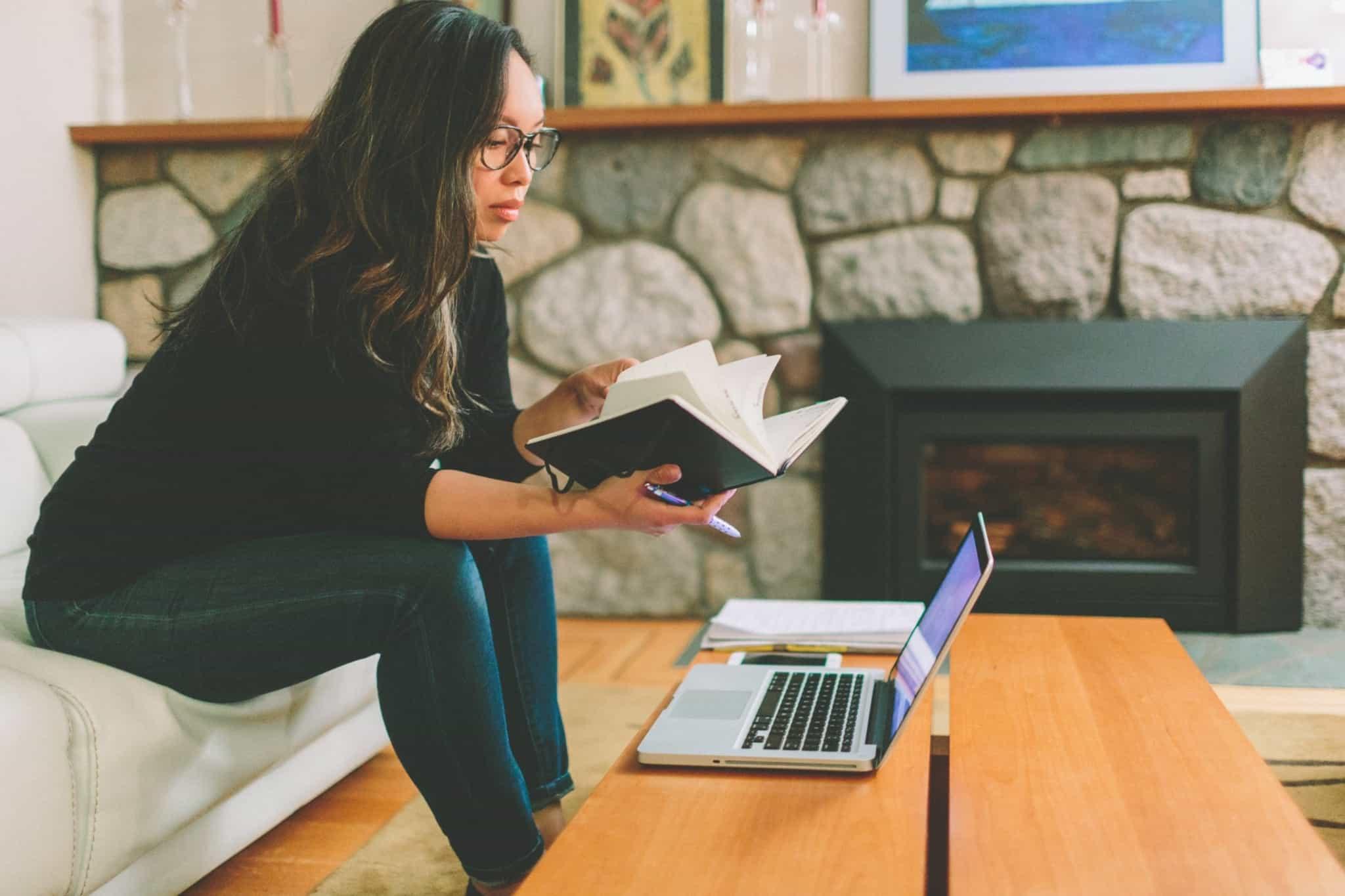 rapariga a trabalhar em casa sentada no sofá e com o computador em cima da mesa