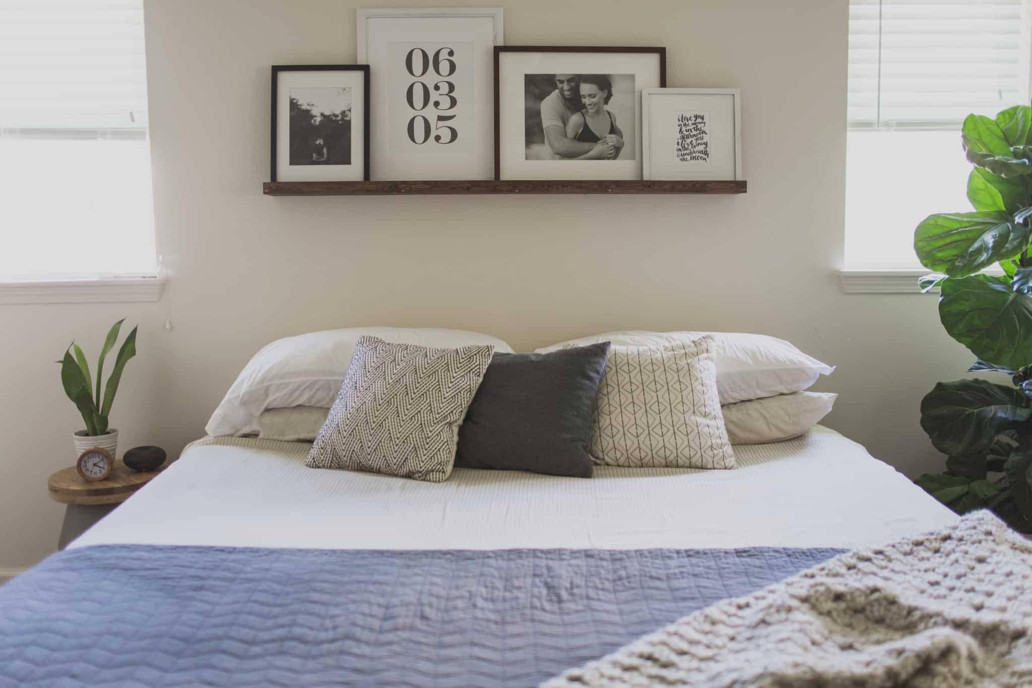 quarto com cama com três almofadas e molduras em cima