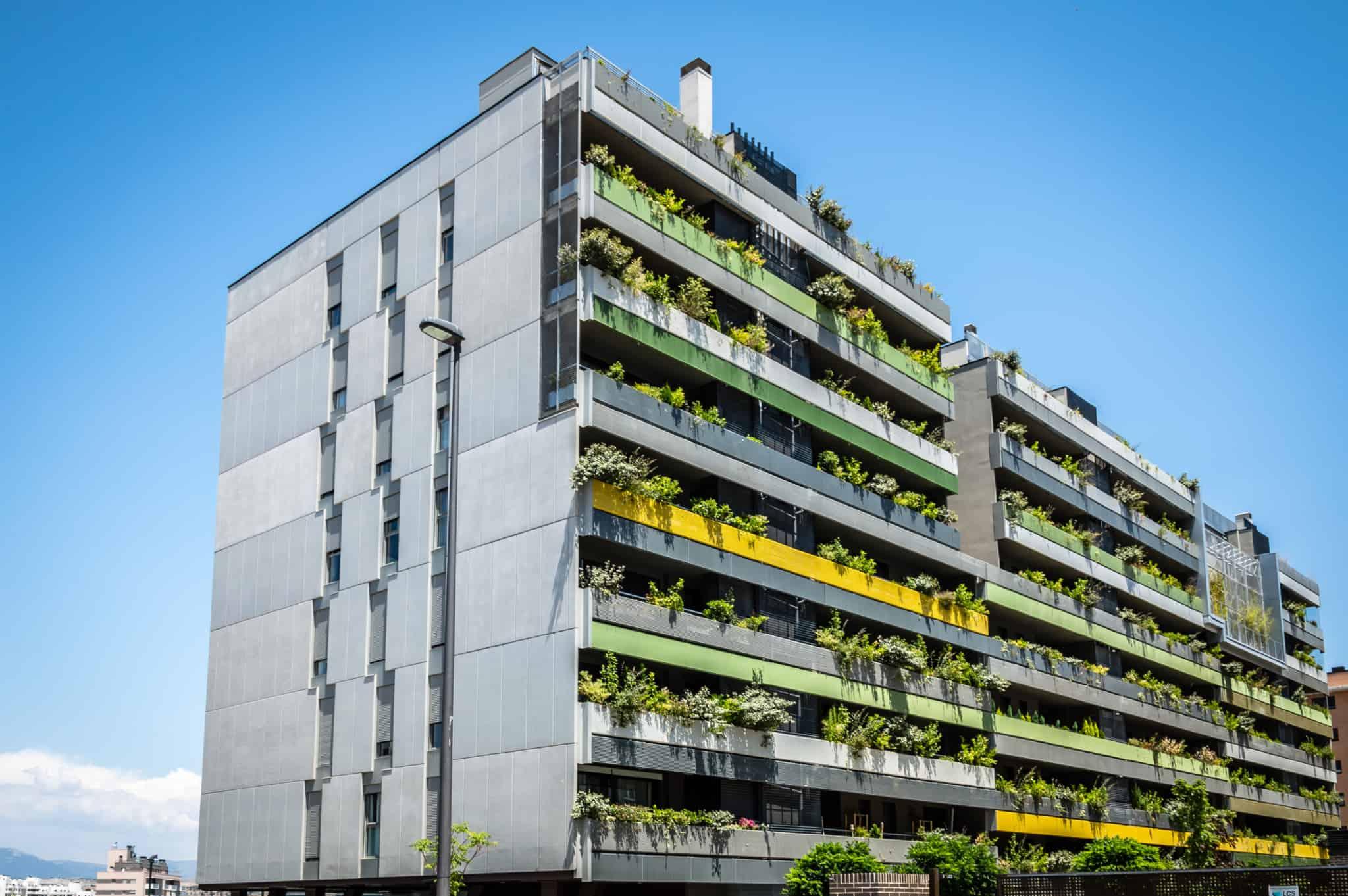 prédio moderno com varandas com plantas e 8 andares